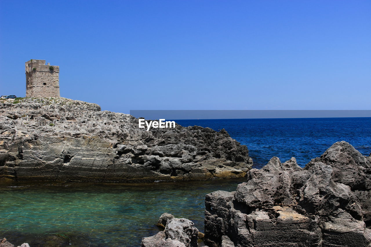 rock - object, sea, clear sky, blue, water, copy space, nature, scenics, horizon over water, day, beauty in nature, no people, outdoors, architecture, sky