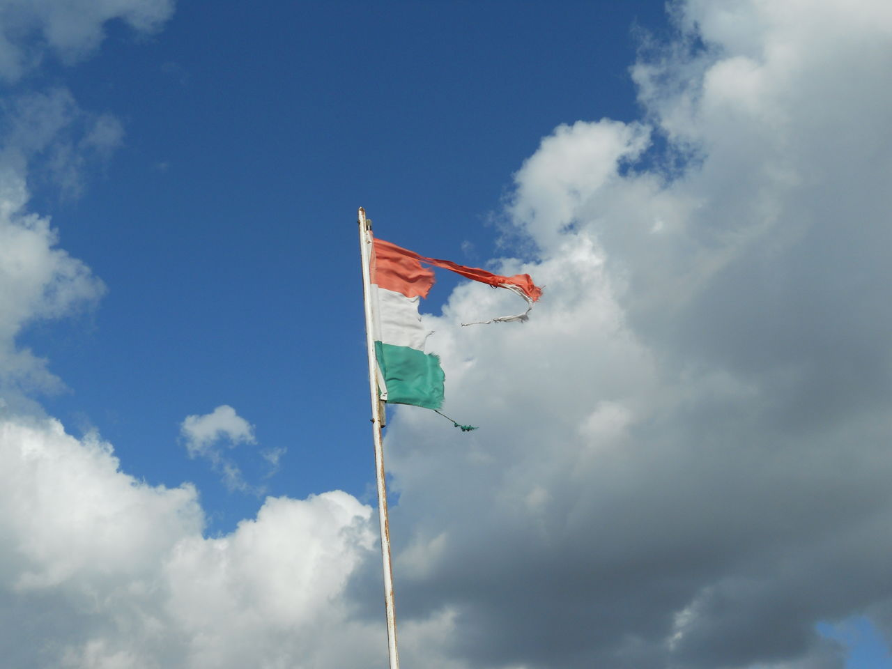 Low angle view of torn indian flag against sky