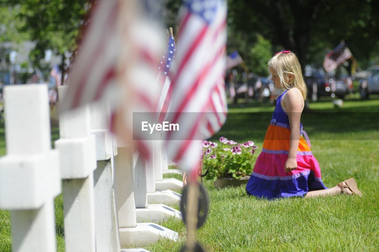 Side View Of Girl Kneeling By Tombstones In Cemetery