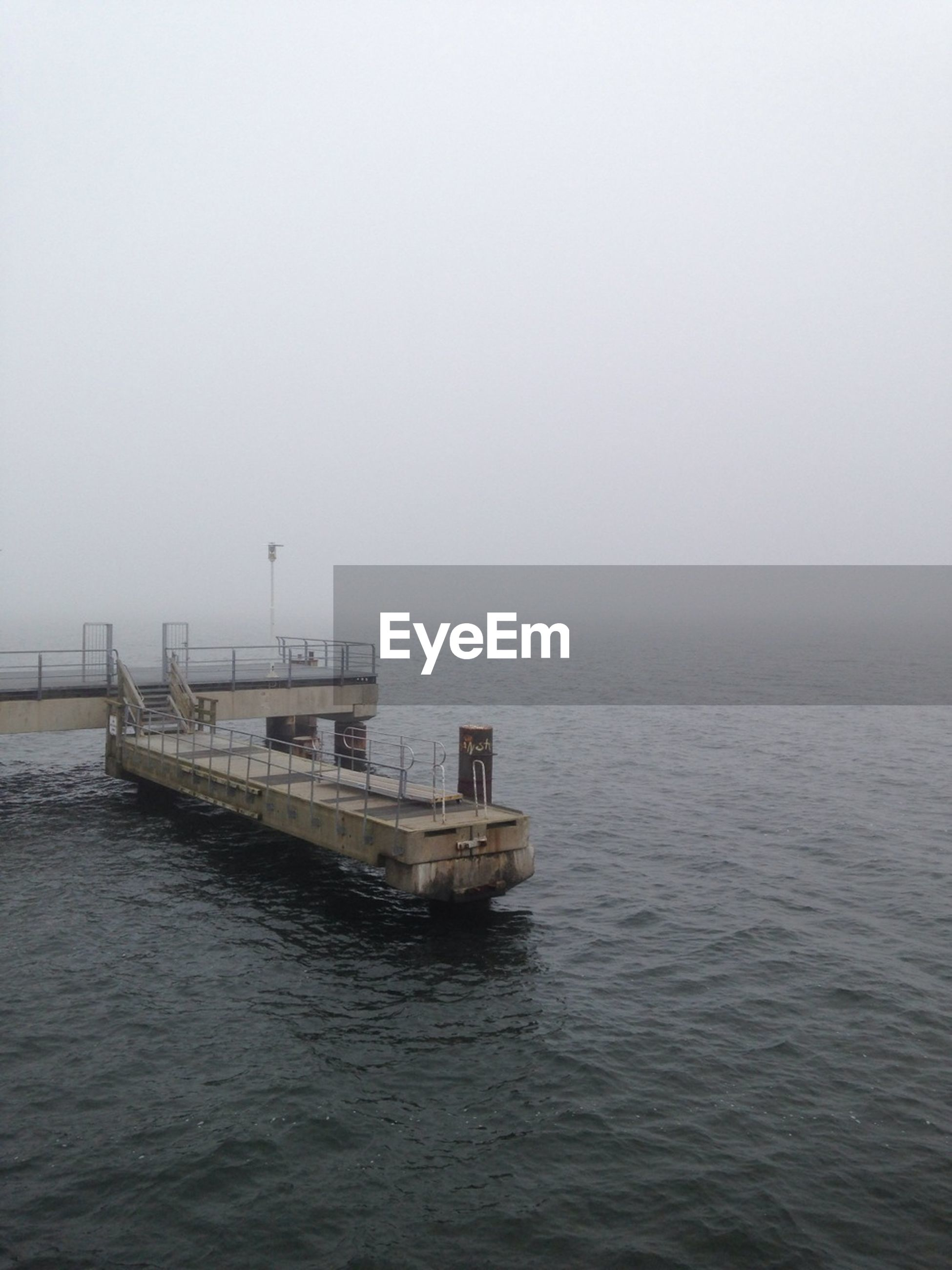 Pier over sea against sky during foggy weather