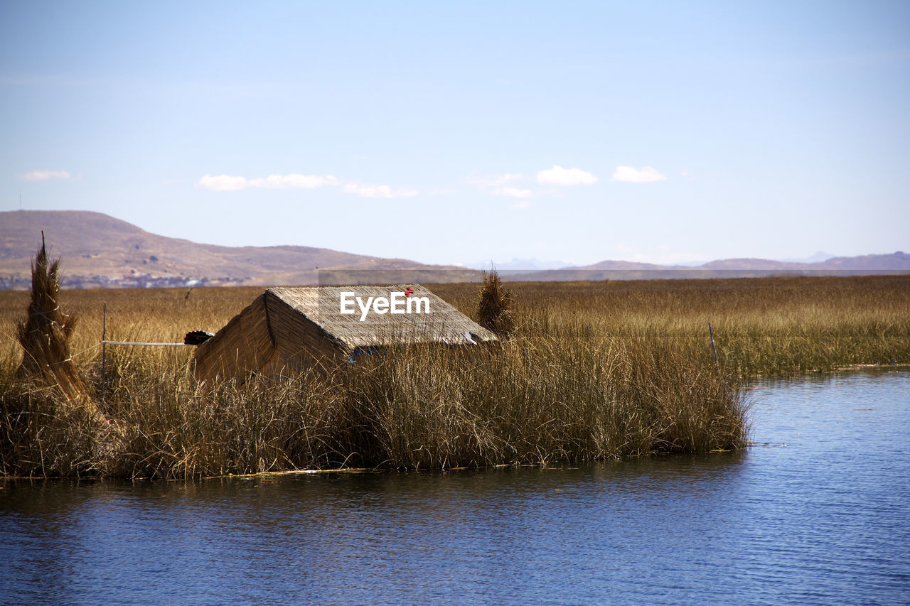 sky, water, house, architecture, built structure, building, tranquility, building exterior, nature, beauty in nature, no people, tranquil scene, scenics - nature, day, plant, environment, grass, lake, landscape, outdoors, cottage