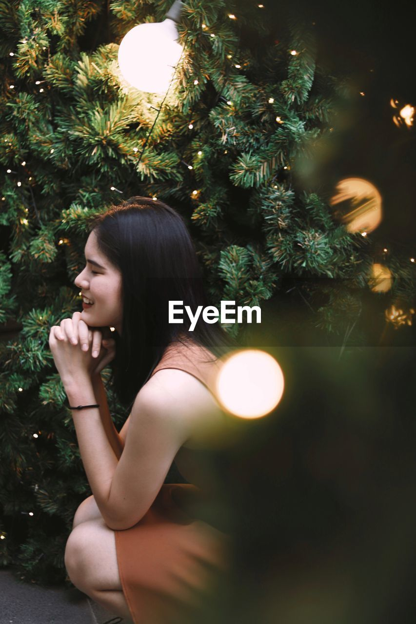 Side view of woman close her eyes under christmas trees