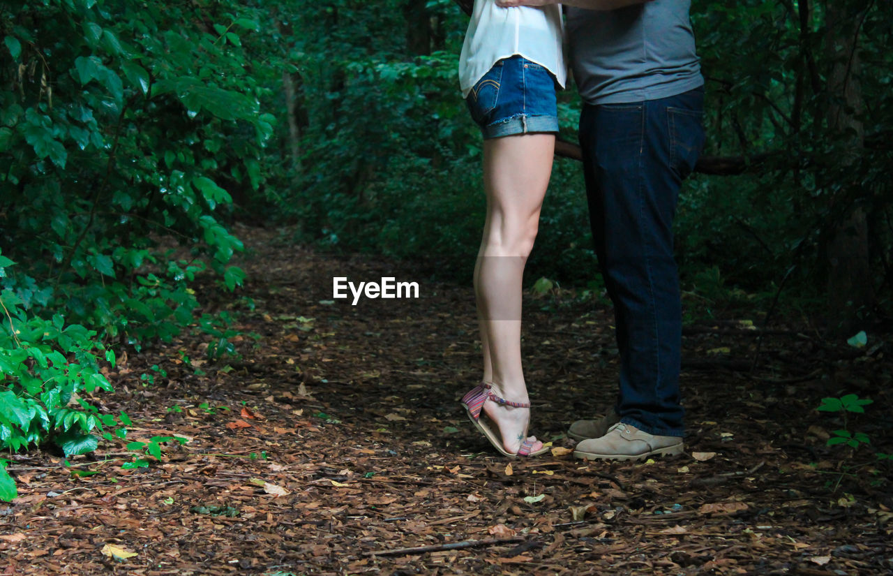 Low Section Of Couple Standing In Forest