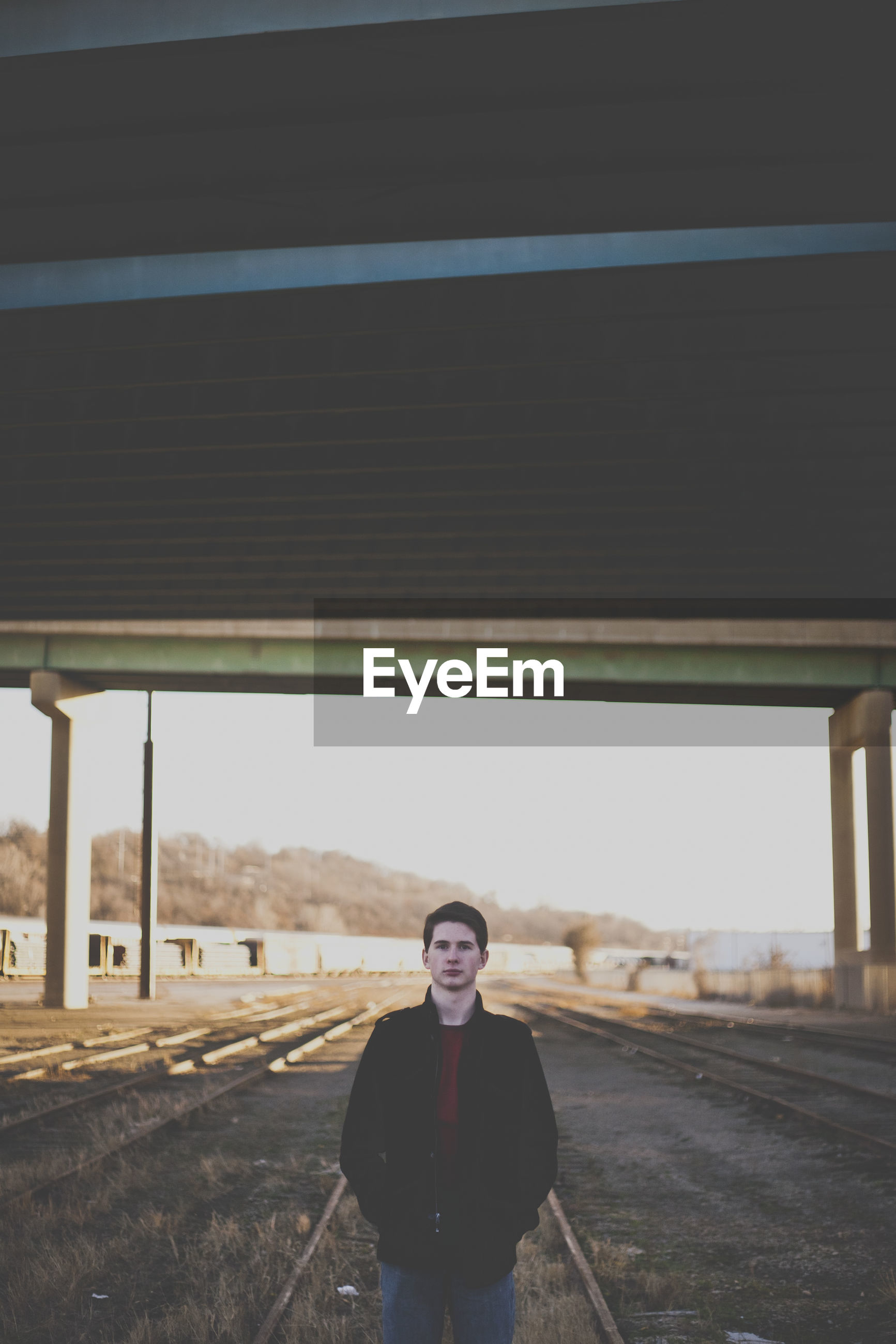 Portrait of handsome man standing at abandoned tracks