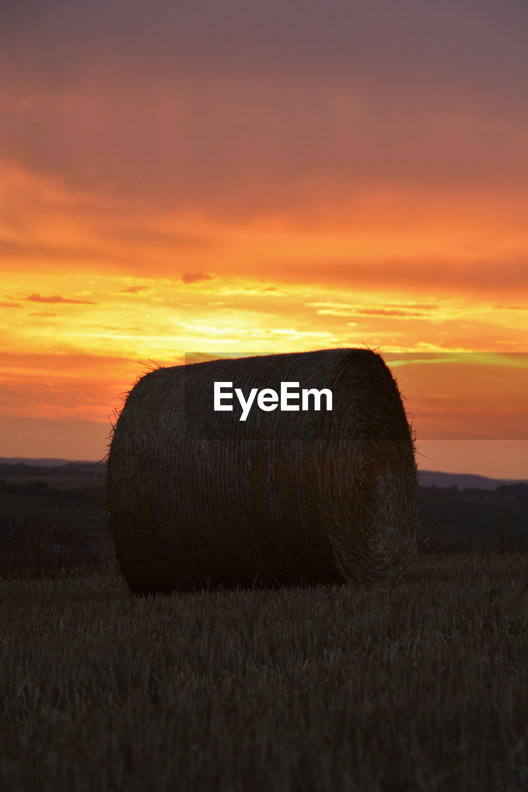 Hay bale on agricultural field against sky during sunset