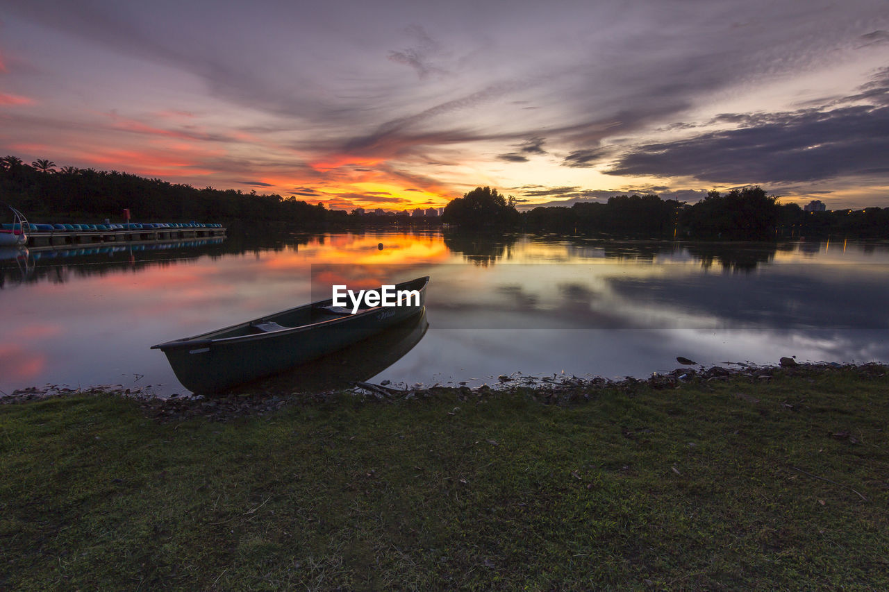 Boat moored on lake against sky during sunset