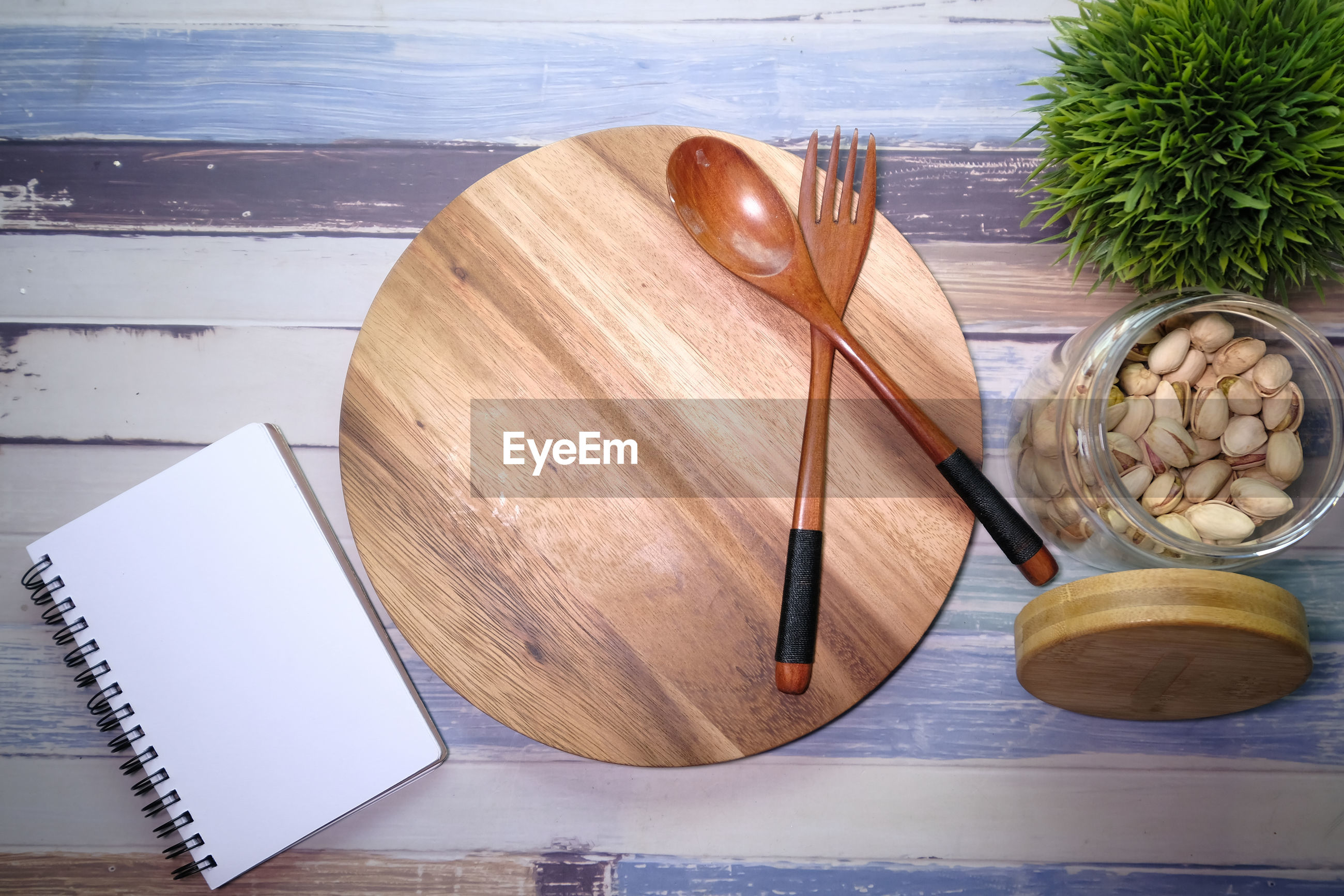 Chopping board with wooden fork and spoon on white table