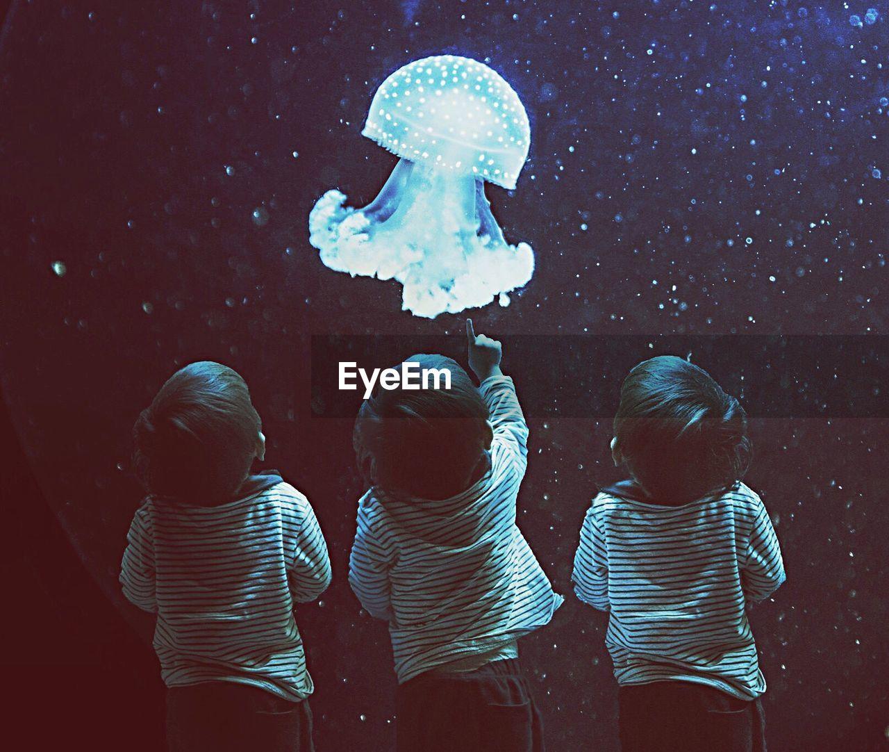 Multiple Image Of Boy Looking At Jellyfish In Aquarium