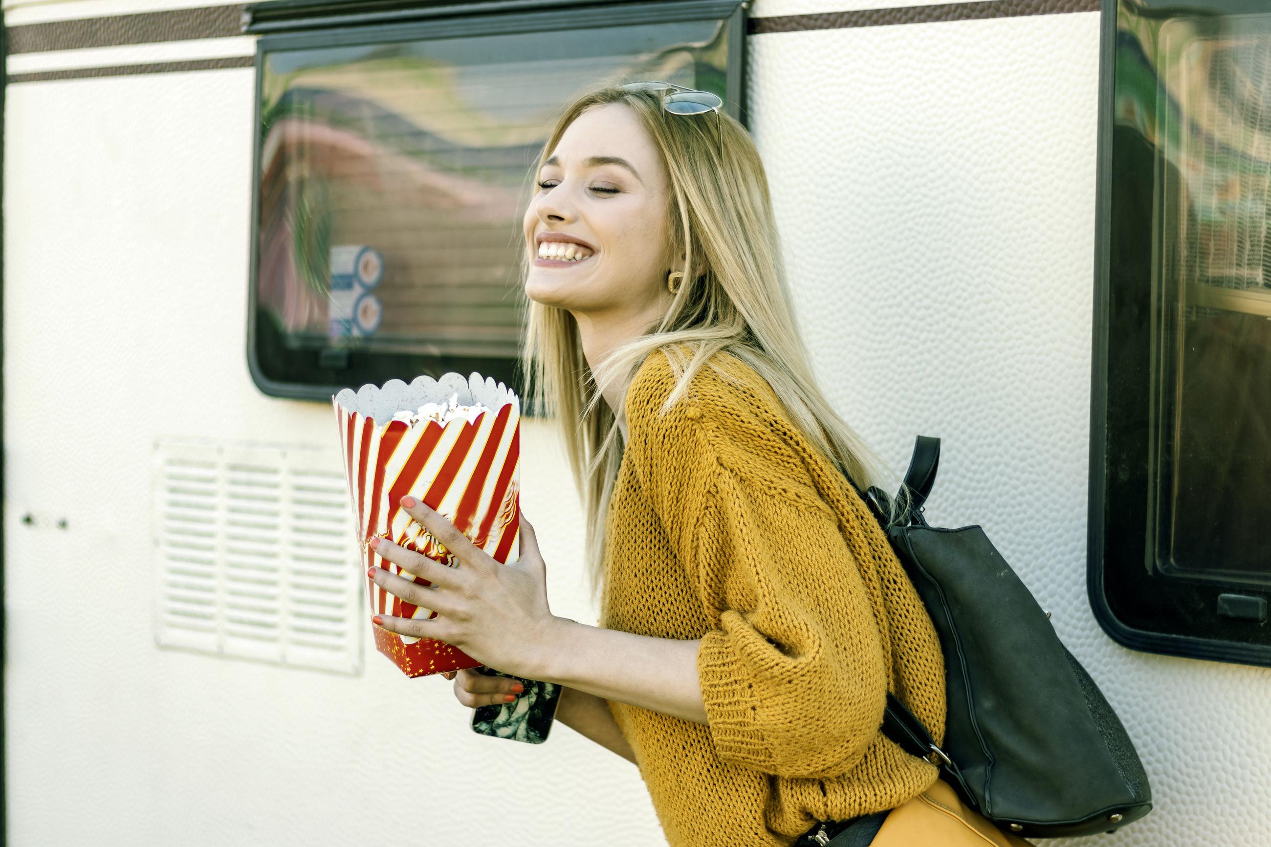 Smiling woman having popcorn in city