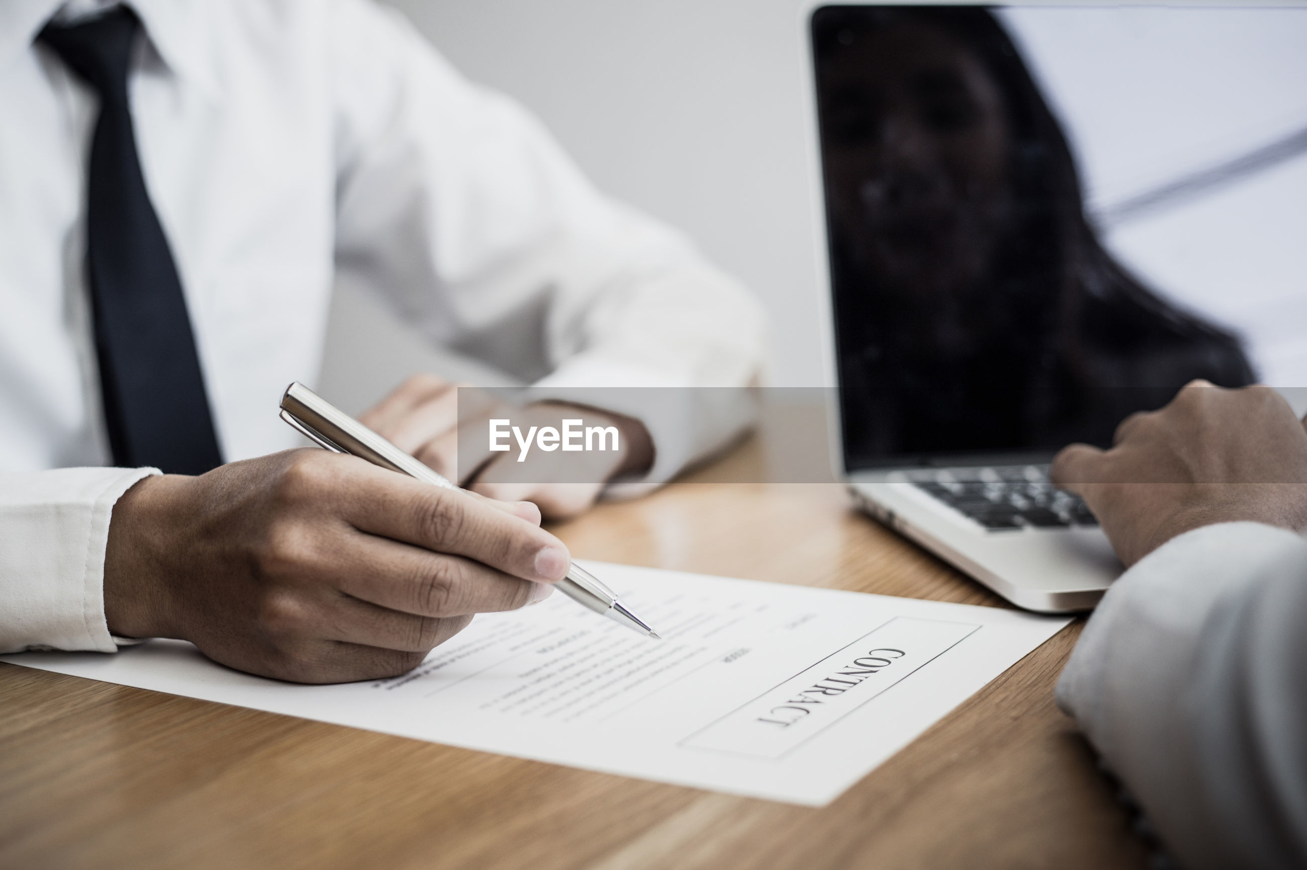 Midsection of businessman with contract at desk in office