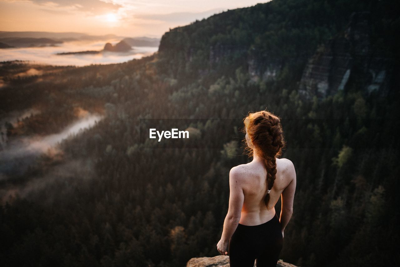 Rear View Of Shirtless Woman Standing Against Mountain