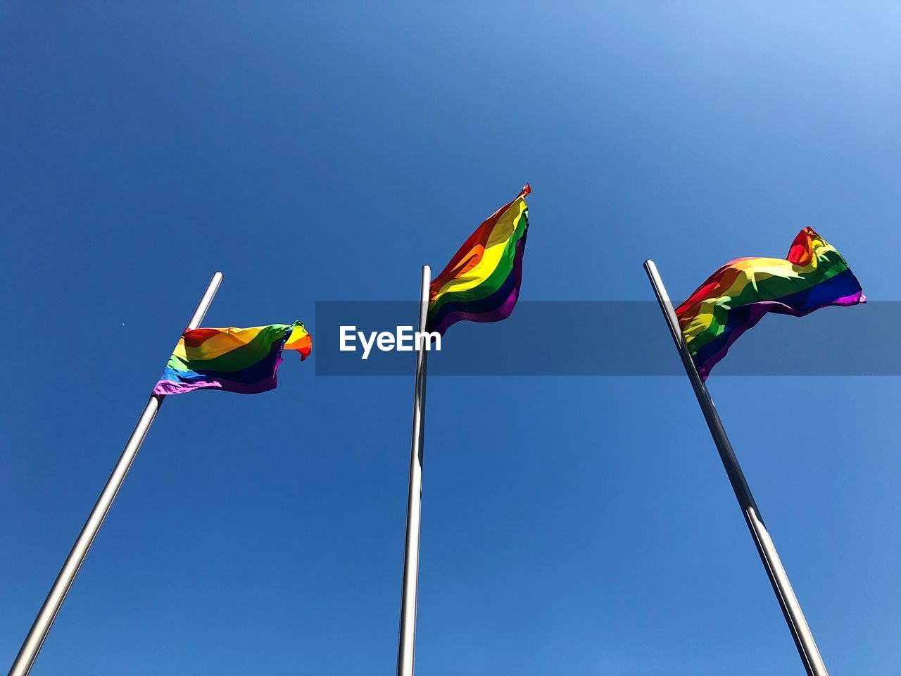 Low Angle View Of Rainbow Flags Against Clear Blue Sky