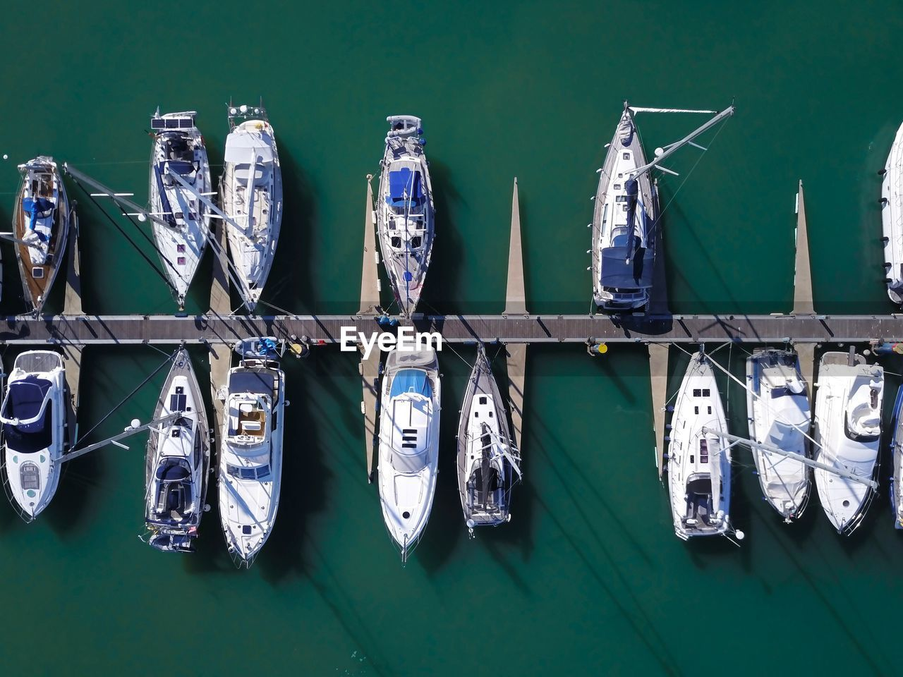transportation, nautical vessel, no people, side by side, mode of transportation, in a row, day, green color, water, outdoors, large group of objects, blue, moored, travel, clothing, arrangement, still life, high angle view, directly above, sailboat