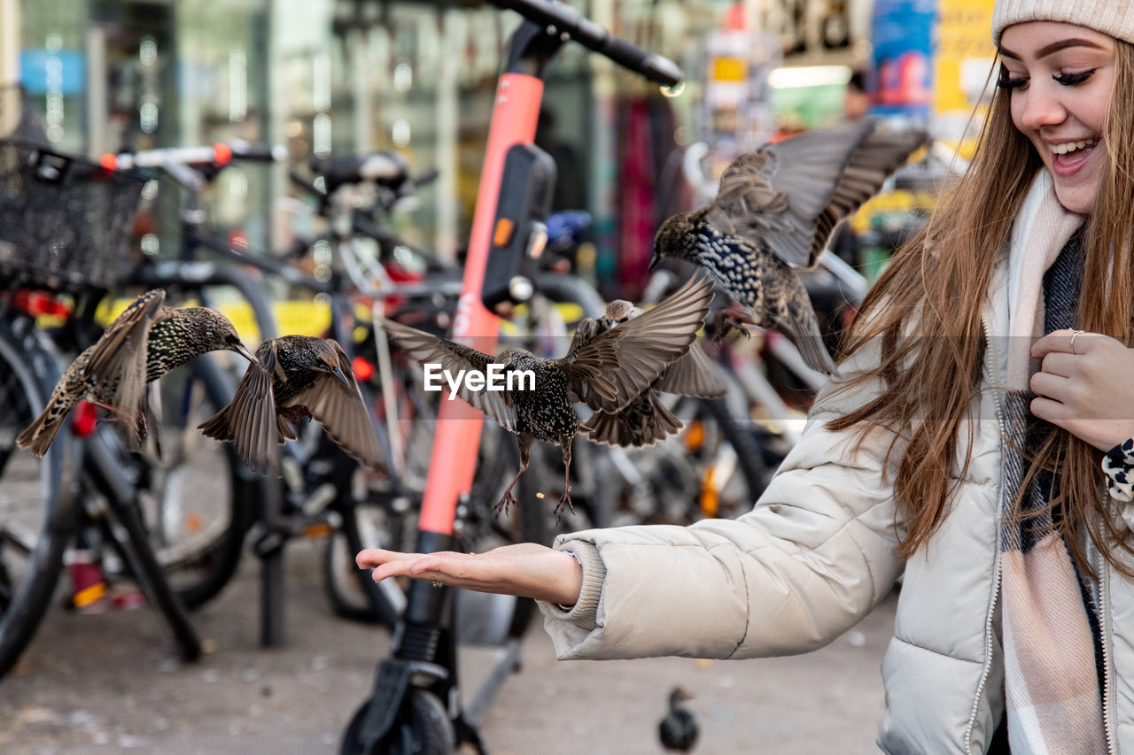 women, real people, young adult, lifestyles, leisure activity, focus on foreground, bicycle, young women, transportation, one person, adult, smiling, day, hair, mode of transportation, holding, city, choice, retail, outdoors, hairstyle, consumerism, bicycle shop