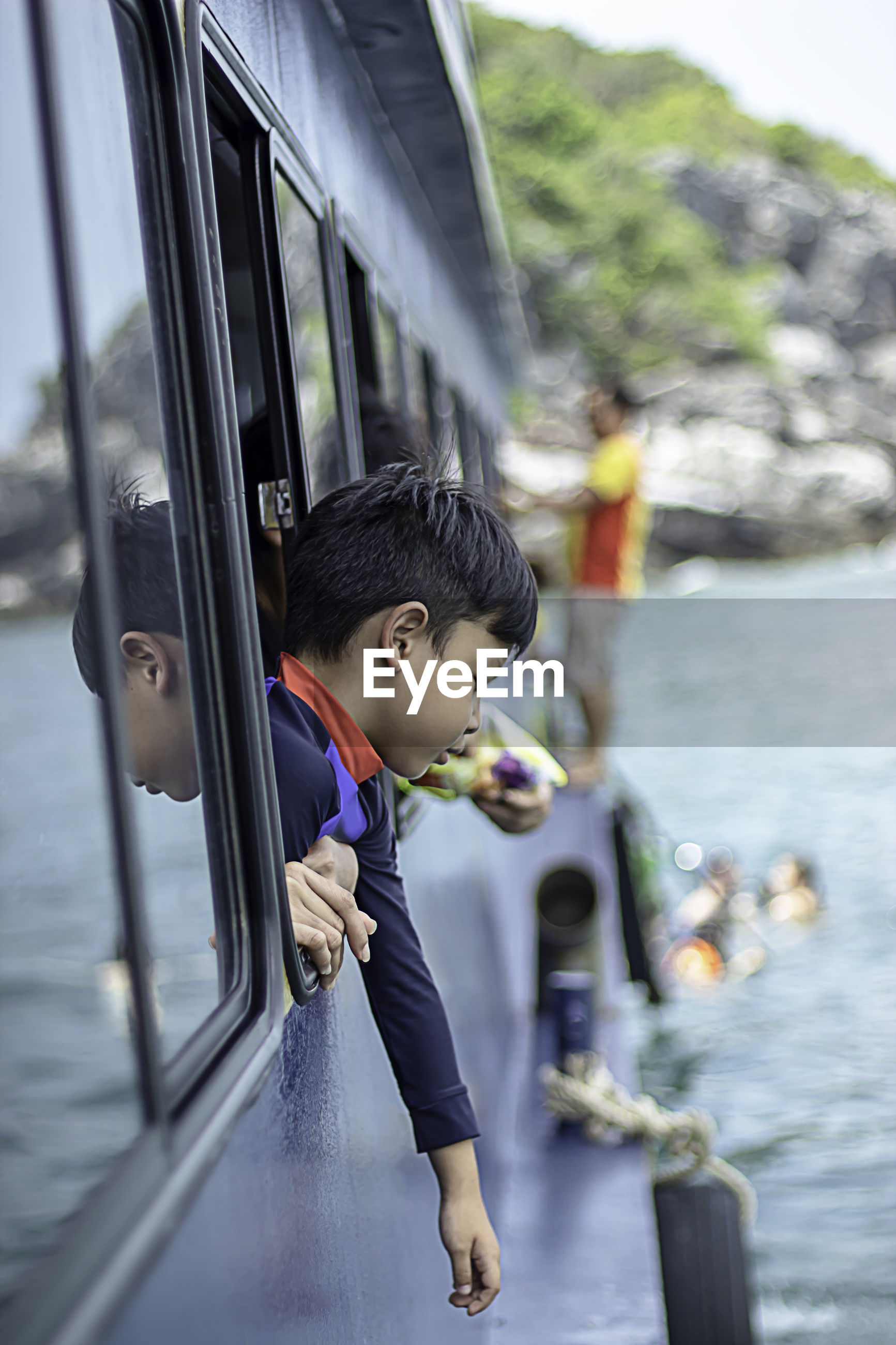 Boy looking away while peeking out from boat window in sea