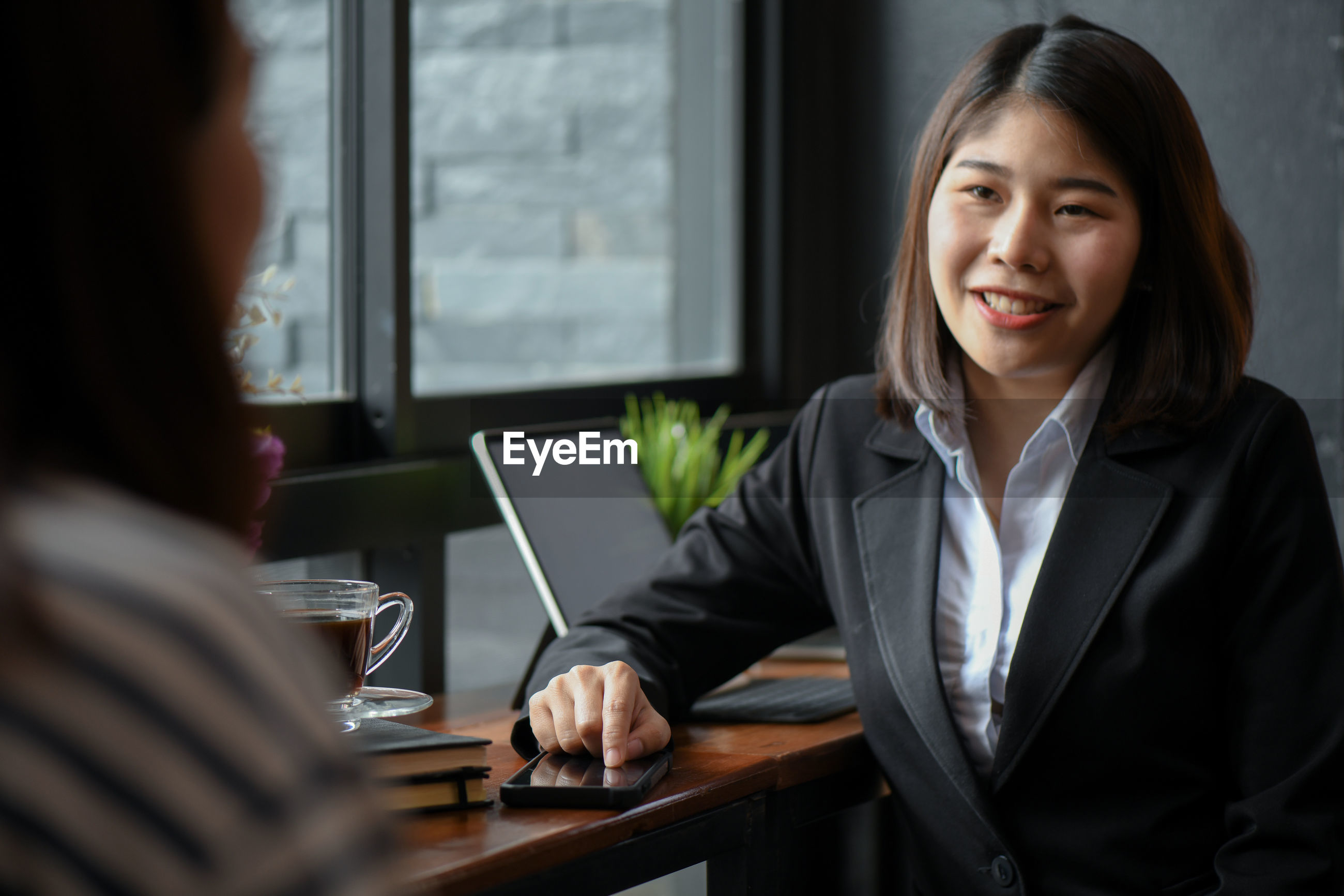 Smiling businesswoman discussing with colleague at office