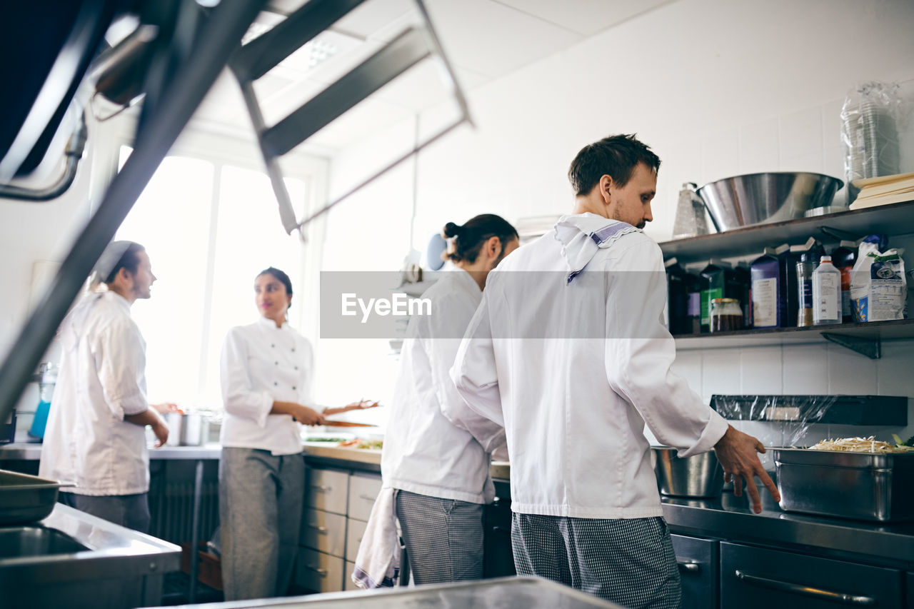 men, three quarter length, occupation, standing, adult, young men, indoors, cooperation, teamwork, healthcare and medicine, young adult, lab coat, group of people, people, males, coworker, real people, mid adult, clothing, women, chef