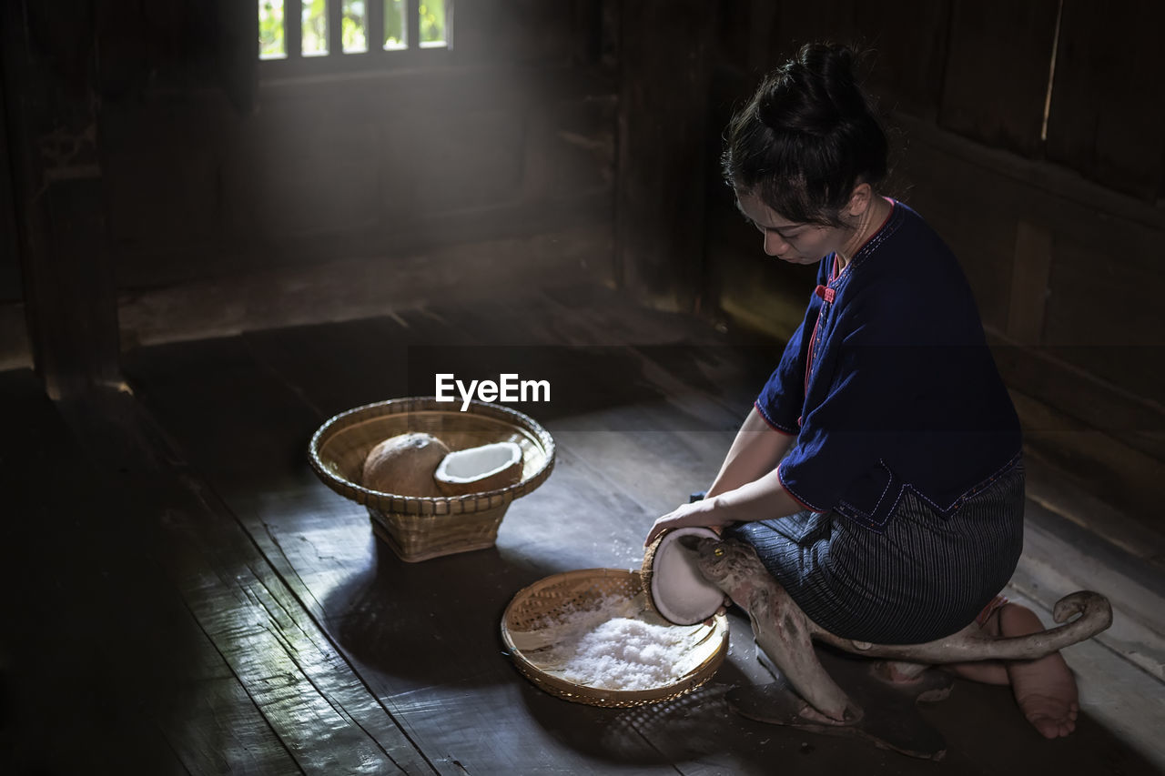 Side view of woman grating coconut at home