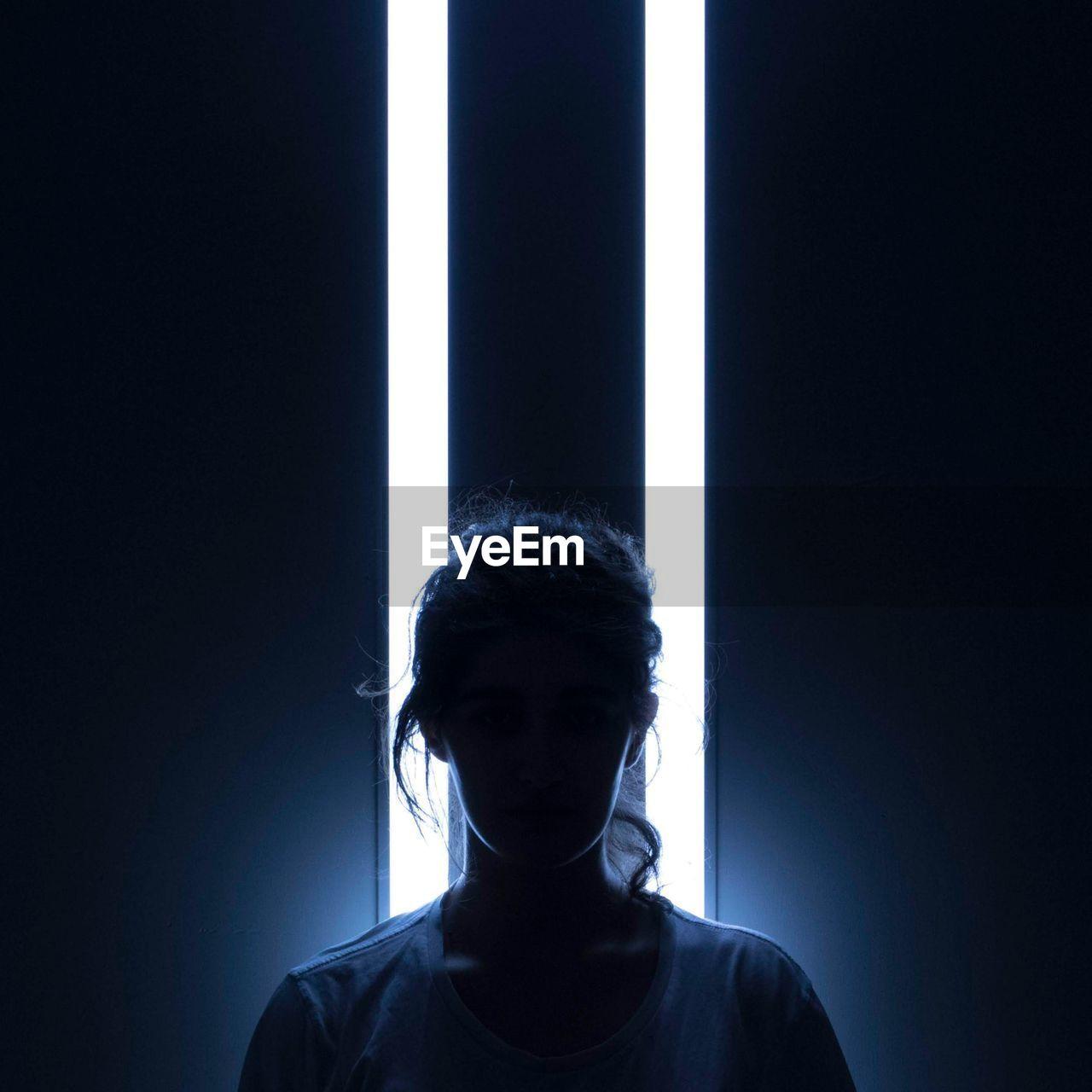 Silhouette Woman Standing Against Illuminated Lighting Equipment In Darkroom