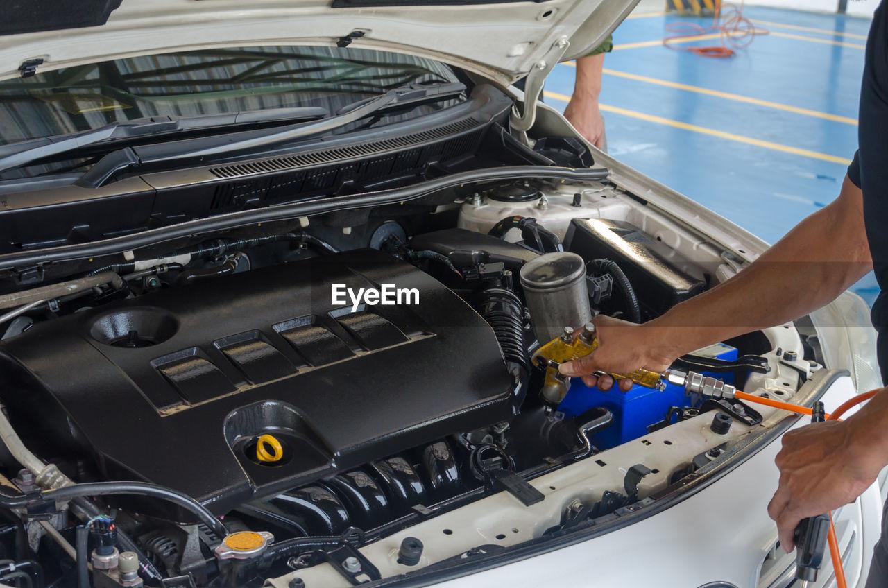 Cropped Image Of Male Mechanic Repairing Car In Auto Repair Shop