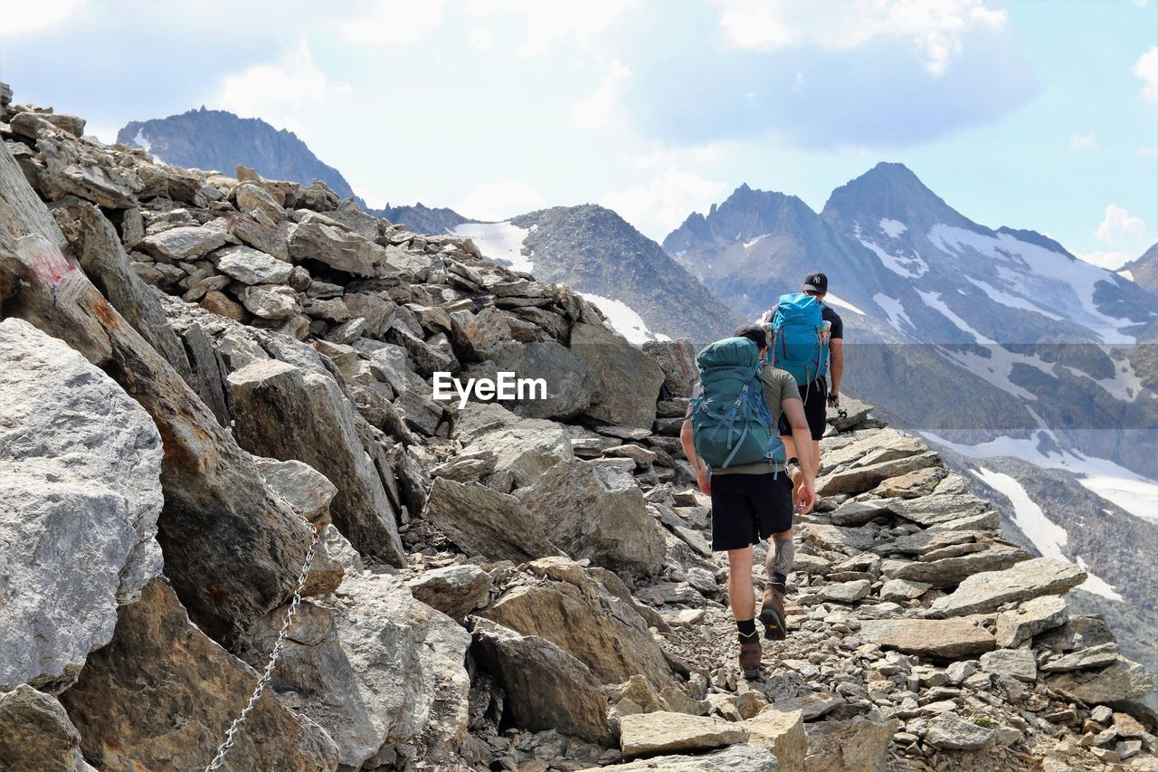 mountain, activity, hiking, leisure activity, rock, adventure, nature, people, rock - object, rear view, climbing, sky, backpack, solid, full length, landscape, mountain range, environment, walking, outdoors, formation