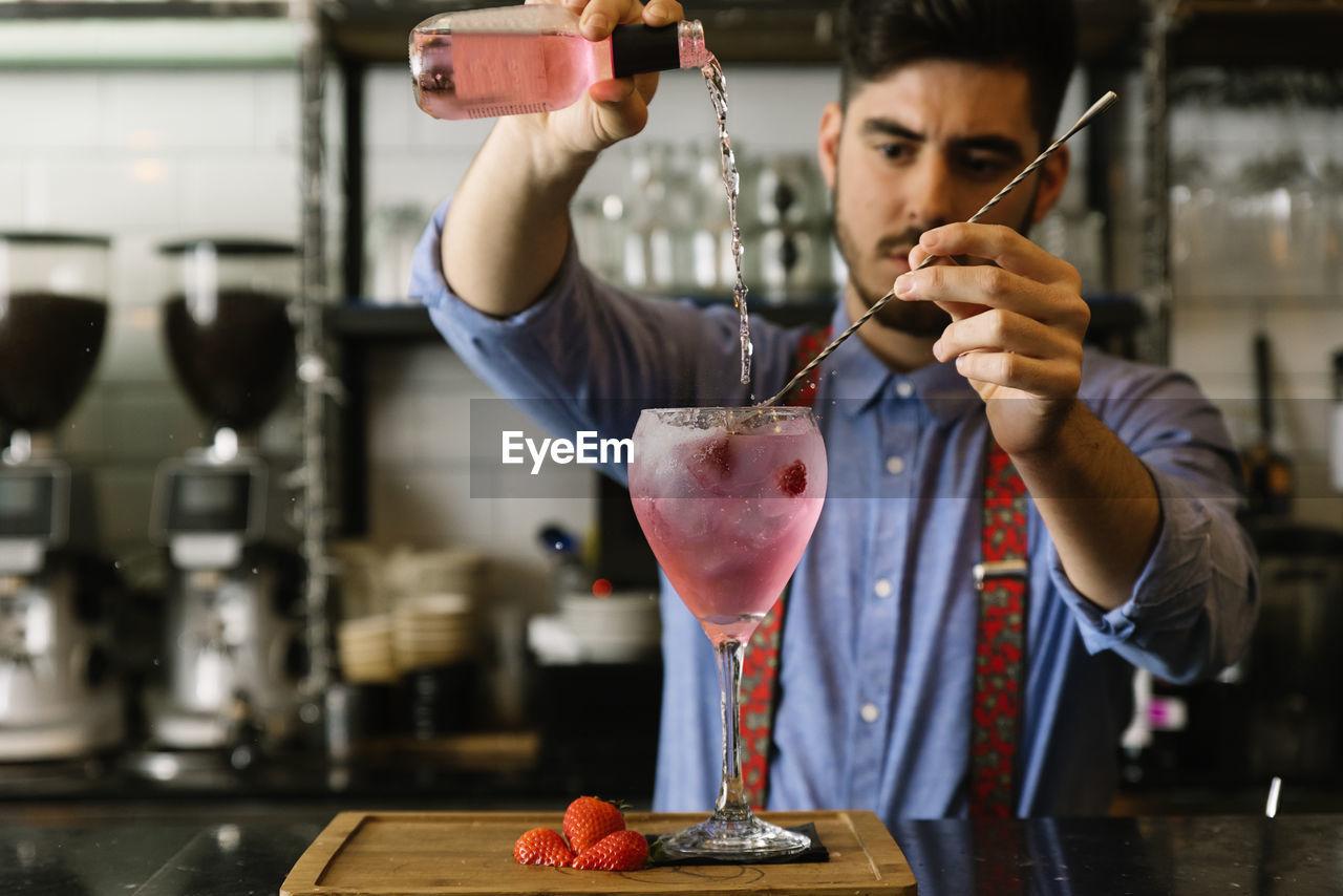 Bartender Preparing Drink In Bar