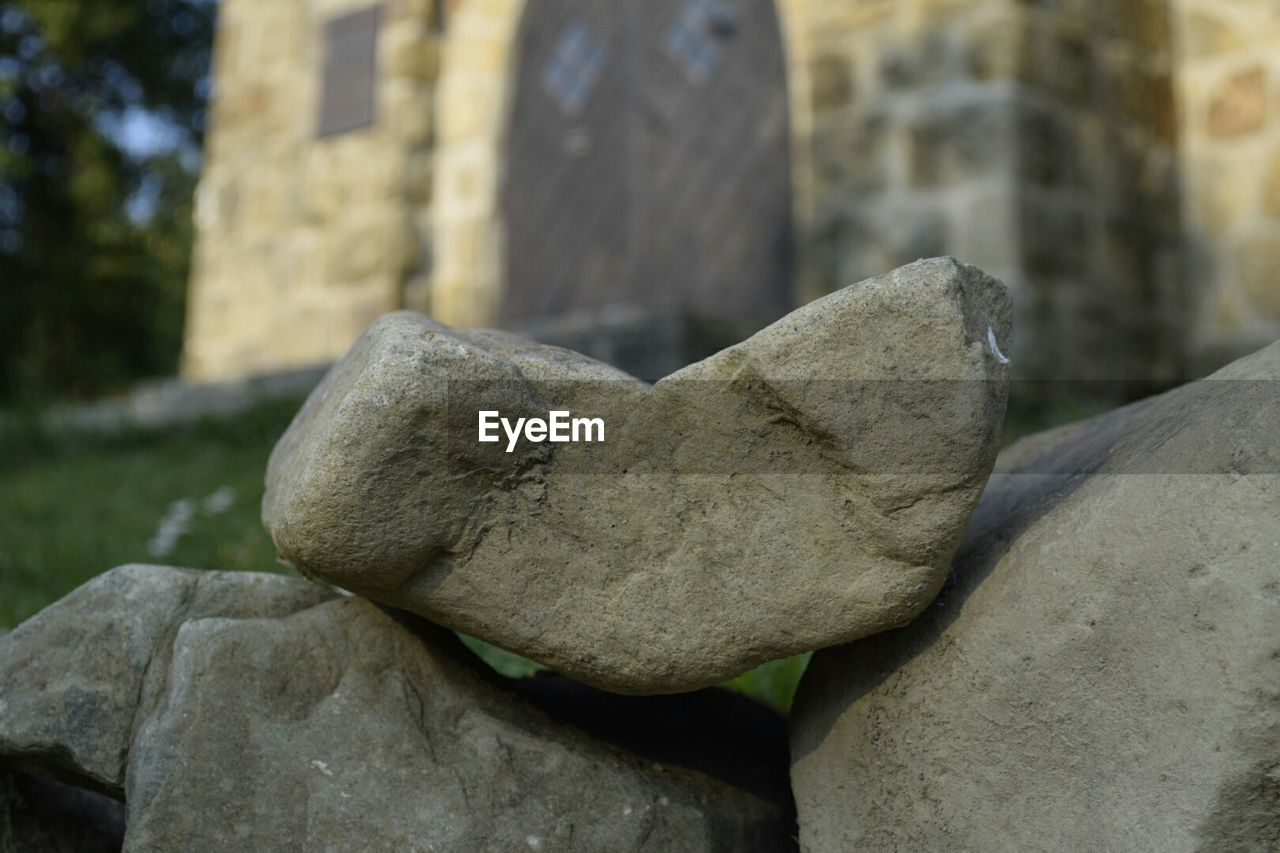 Close-Up Of Stones On Field Against Building
