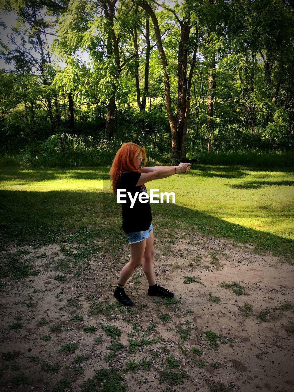 Full Length Of Woman Shooting Gun In Park Against Trees