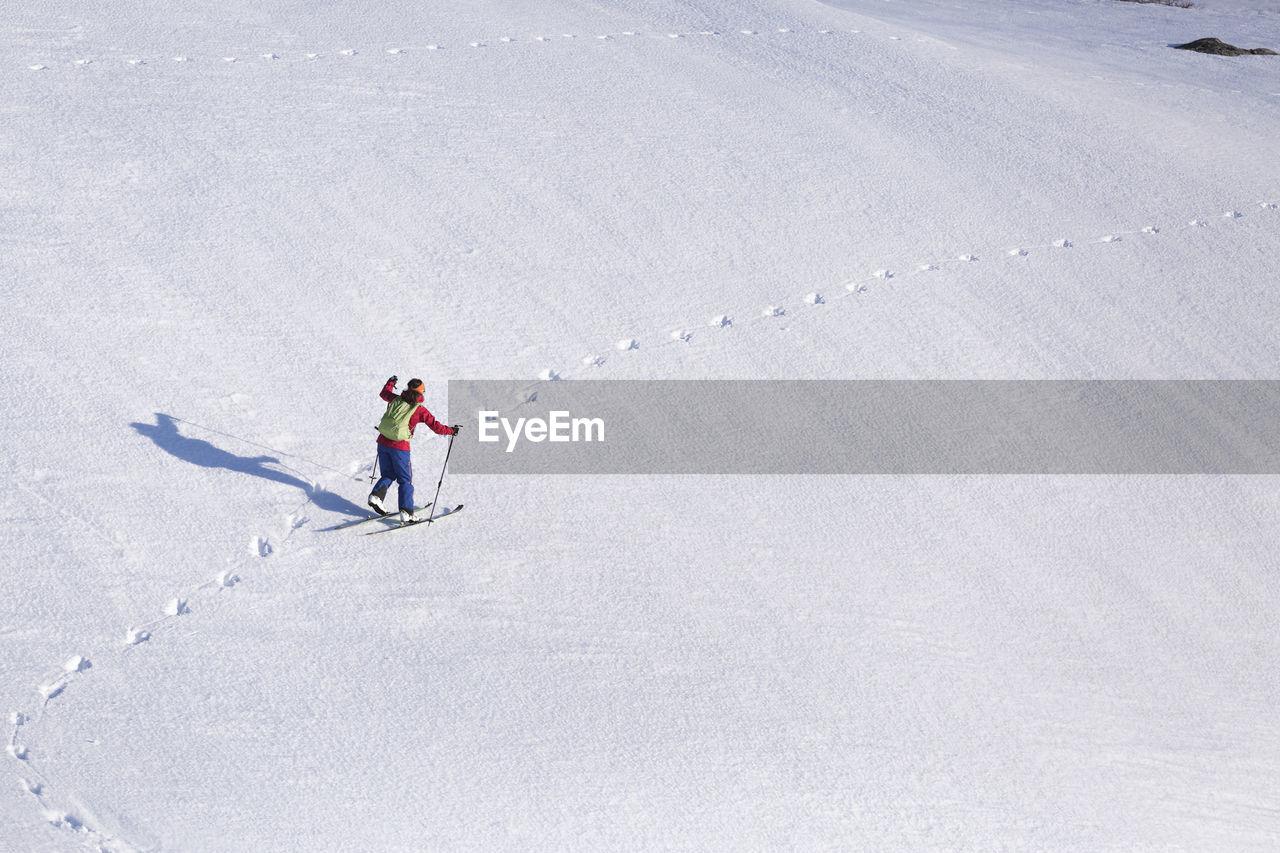 HIGH ANGLE VIEW OF MAN SKIING ON MOUNTAIN