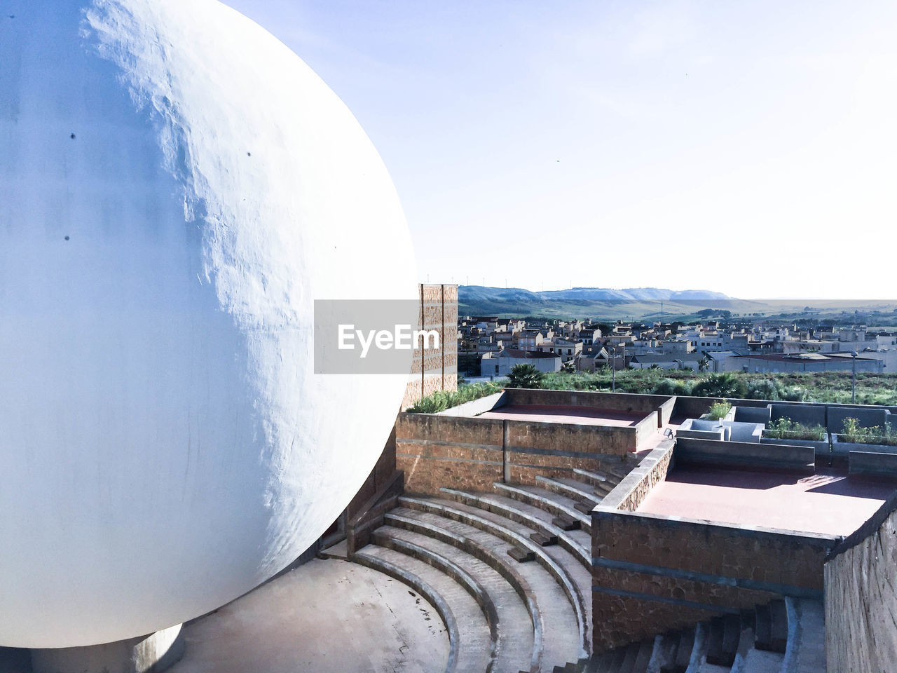 White sphere structure on building terrace against sky