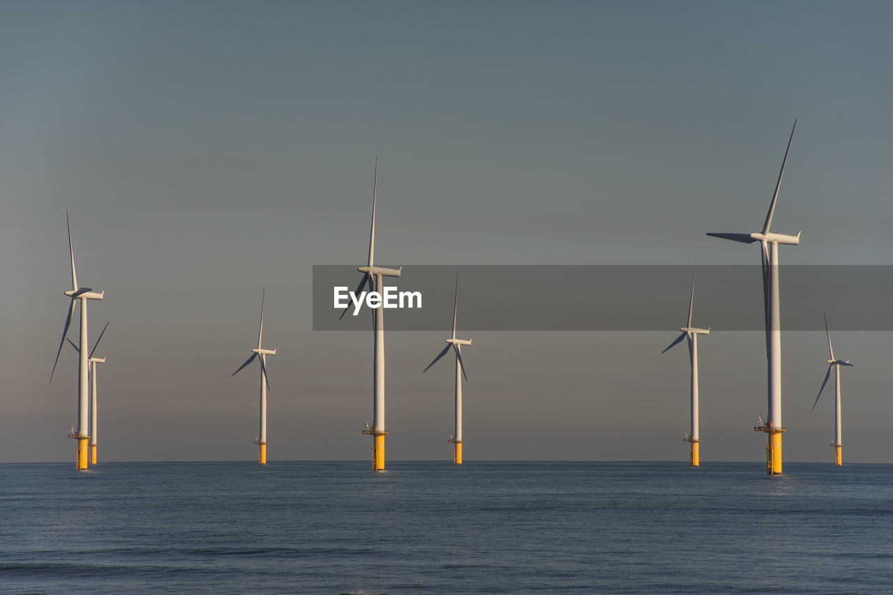 sky, fuel and power generation, wind turbine, renewable energy, turbine, sea, wind power, water, alternative energy, waterfront, environmental conservation, horizon over water, beauty in nature, no people, horizon, scenics - nature, nature, environment, in a row