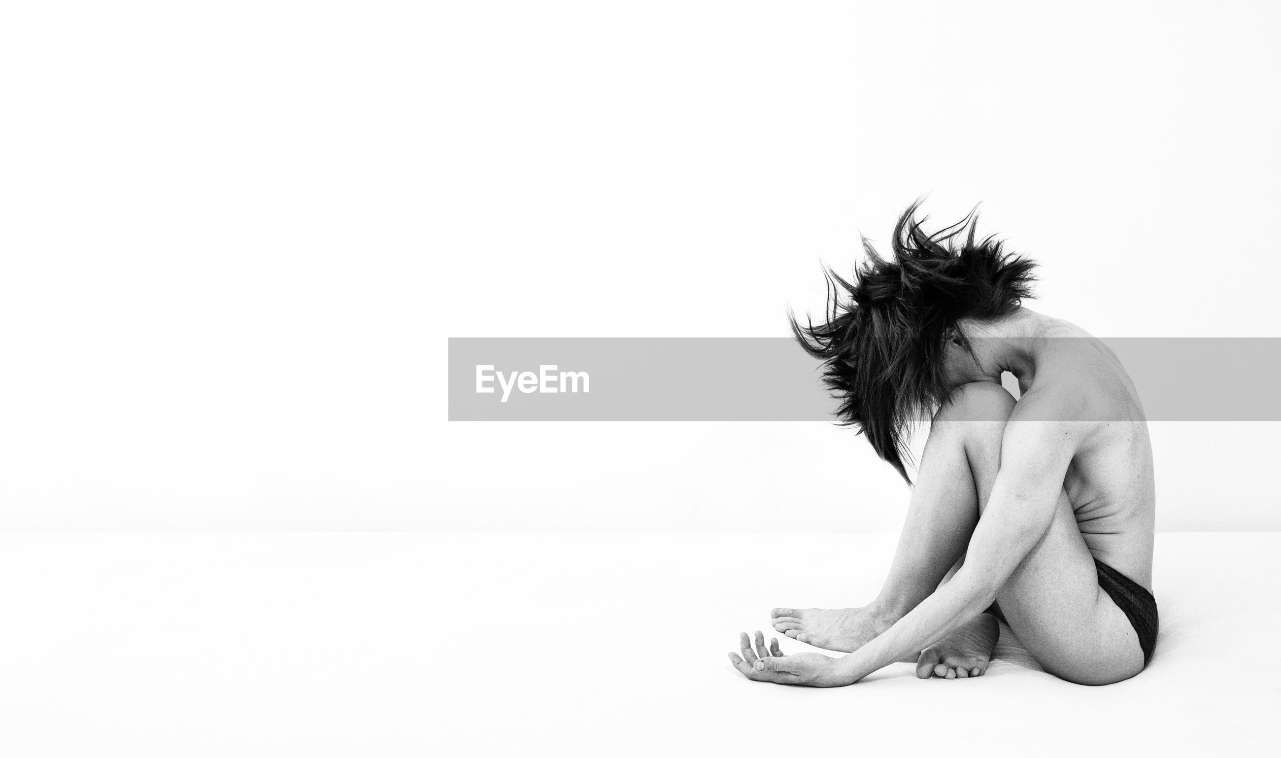 Side view of sensuous woman sitting against white background