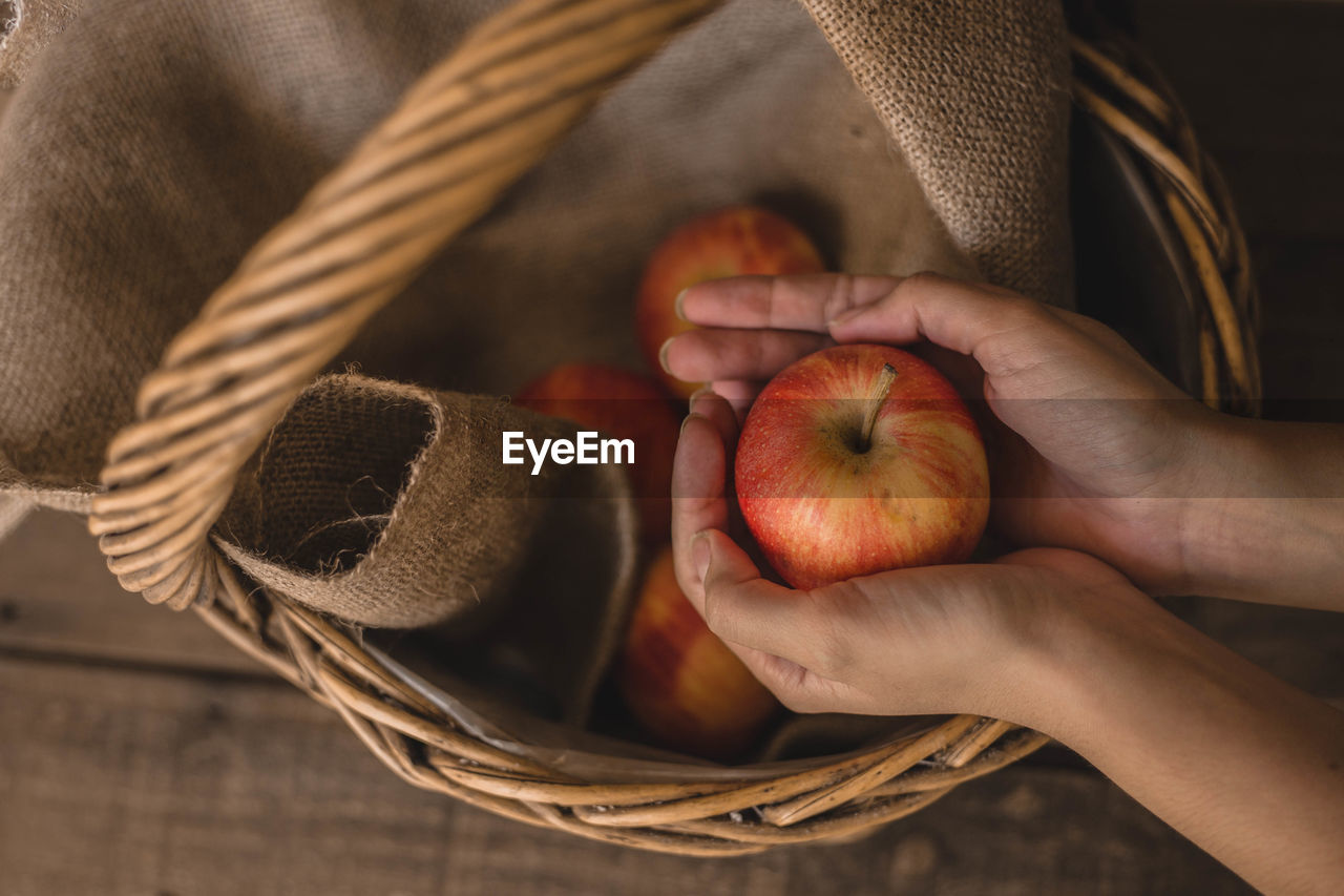 Cropped hands of woman holding apples in basket on table
