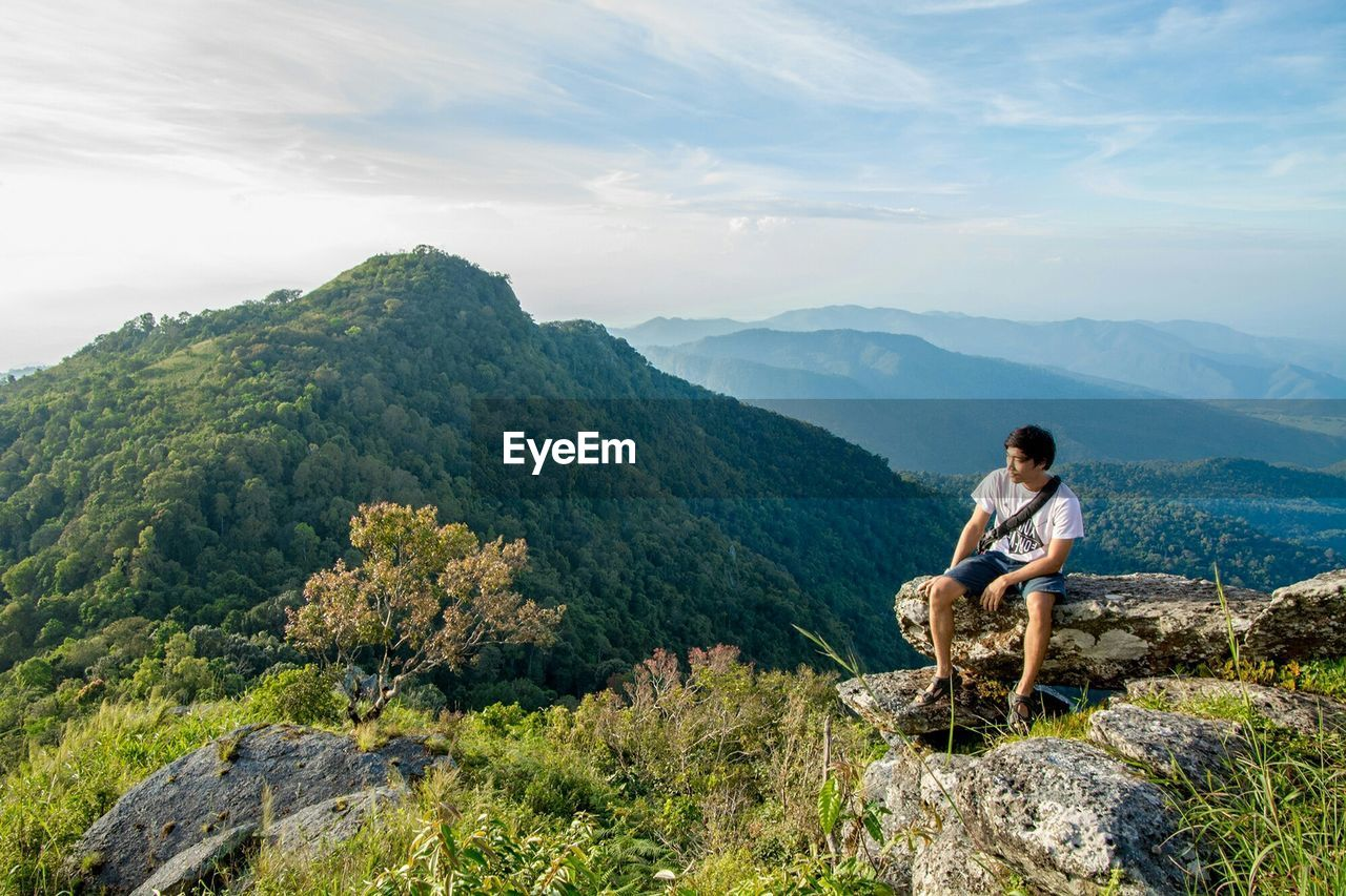 Man looking at mountain while sitting on cliff against sky