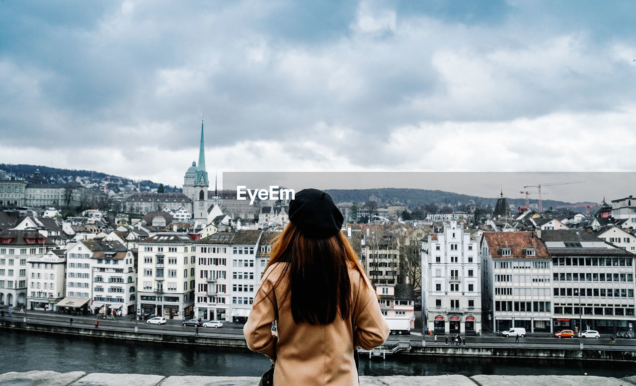 Rear View Of Woman Looking At Cityscape Against Cloudy Sky