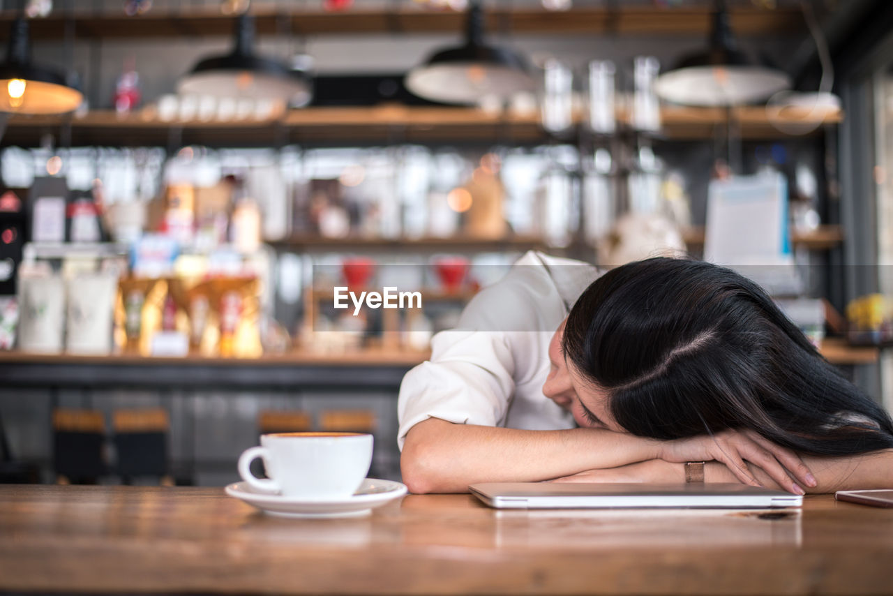Young woman resting at table in cafe
