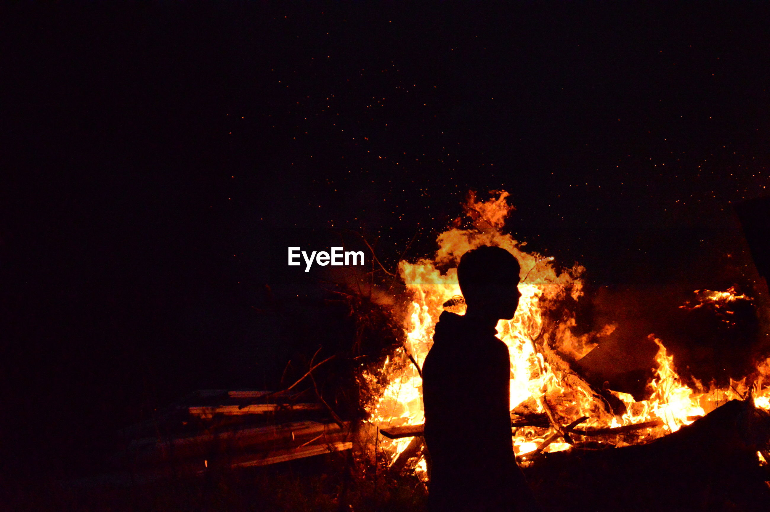 flame, burning, night, real people, heat - temperature, danger, silhouette, one person, men, glowing, motion, standing, outdoors, bonfire, leisure activity, risk, lifestyles, nature, women, sky, people