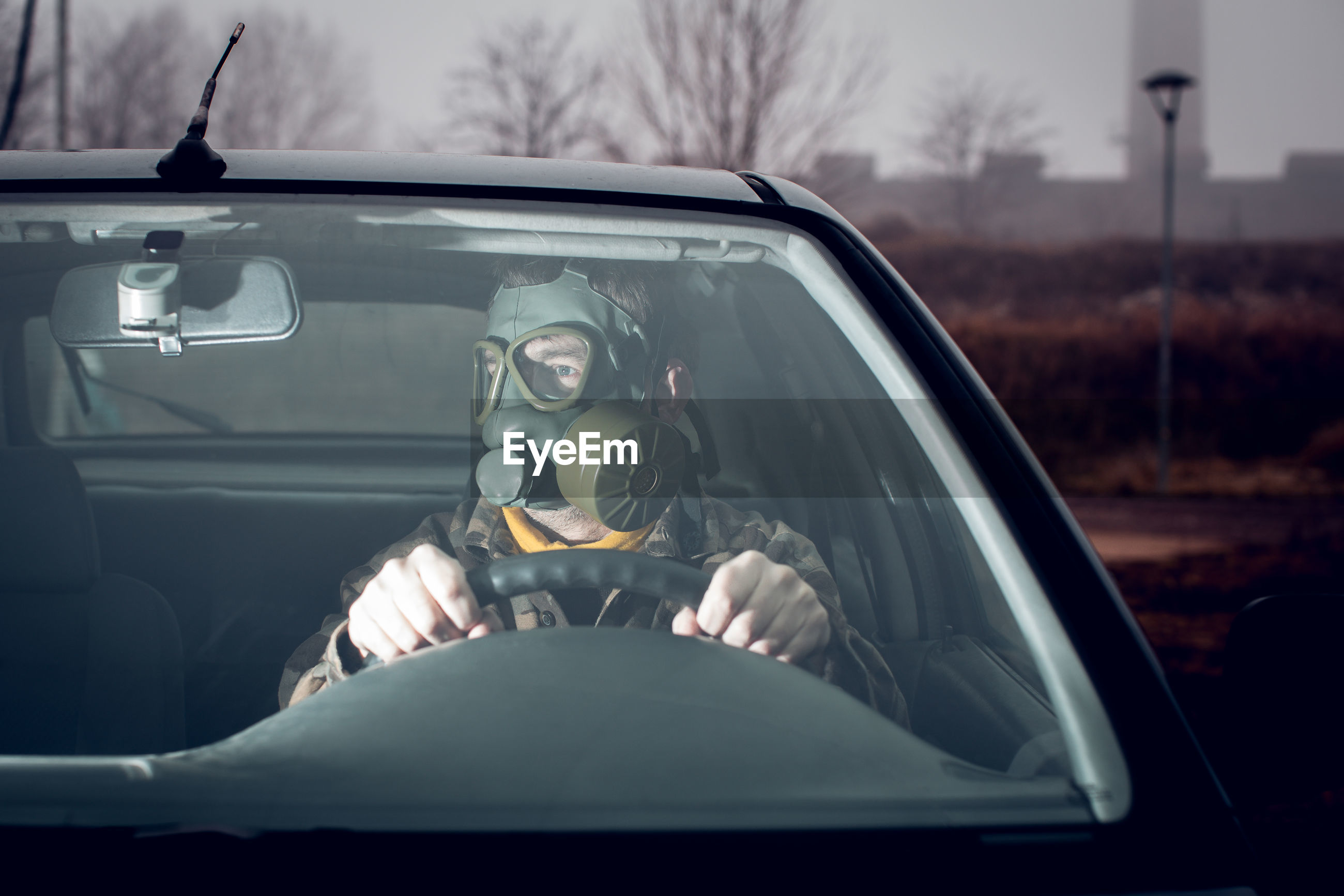 Soldier wearing gas mask driving car
