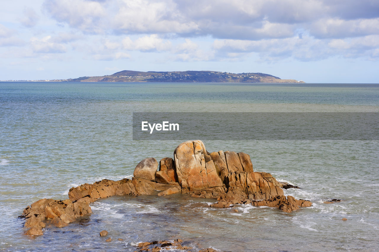 water, sea, sky, scenics - nature, beauty in nature, tranquility, rock, tranquil scene, cloud - sky, nature, rock - object, idyllic, non-urban scene, beach, land, solid, day, no people, rock formation, horizon over water, eroded