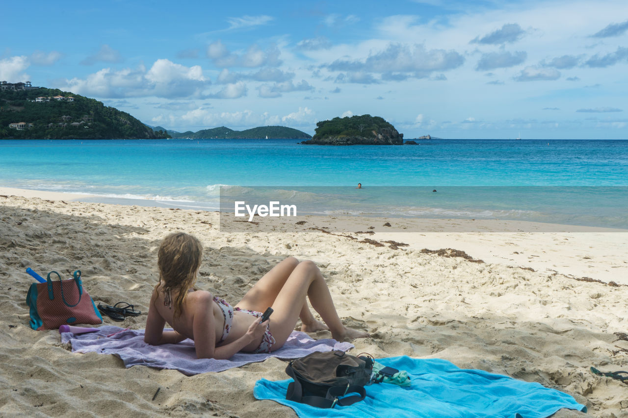 sea, beach, sand, sky, one person, relaxation, water, horizon over water, day, real people, leisure activity, vacations, lying down, beauty in nature, nature, cloud - sky, sitting, outdoors, low section, young adult, full length, young women, women, scenics, people