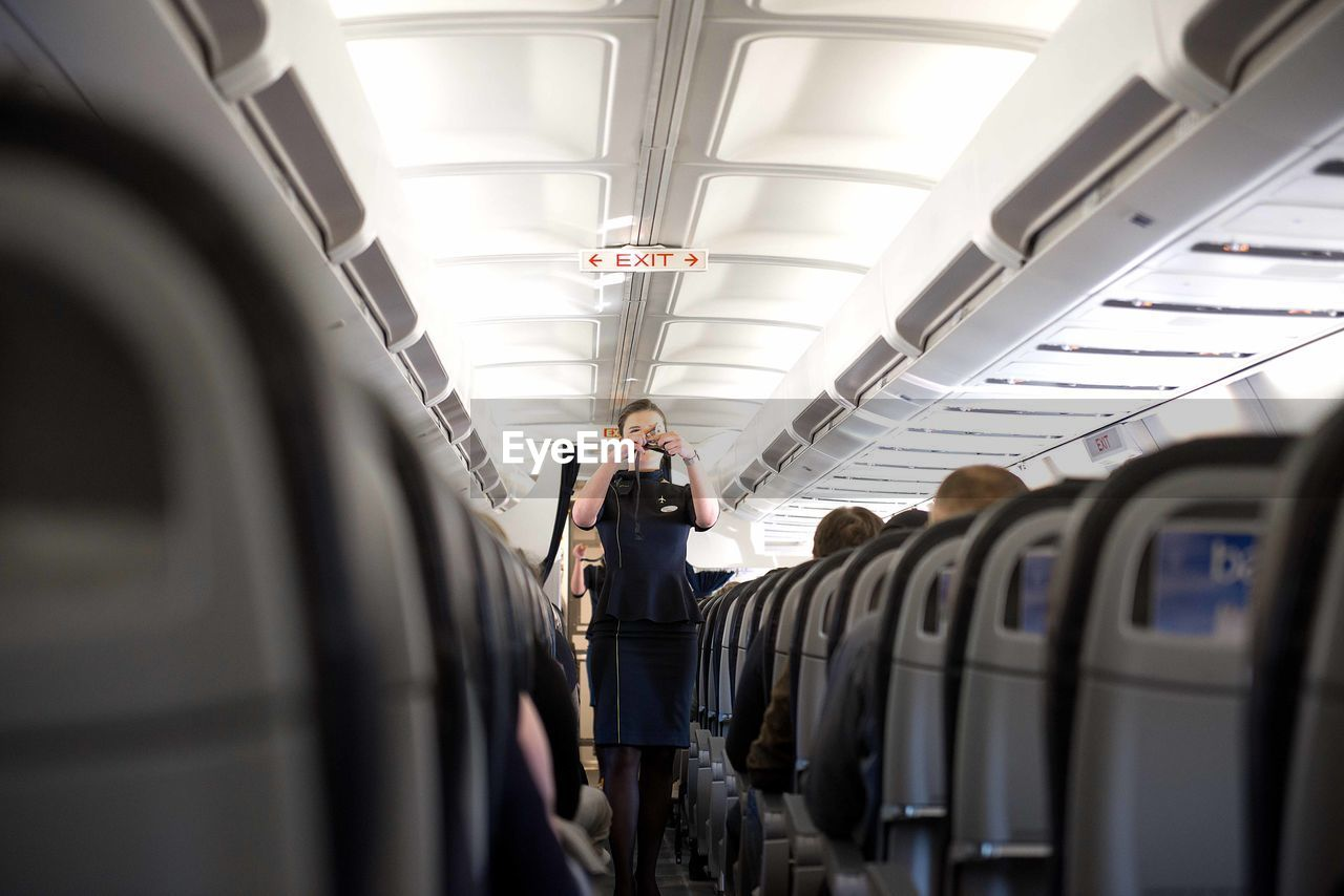 mode of transportation, transportation, vehicle interior, travel, public transportation, airplane, air vehicle, men, vehicle seat, real people, indoors, seat, passenger, adult, lifestyles, standing, selective focus, train, journey, people, airplane seat, luxury