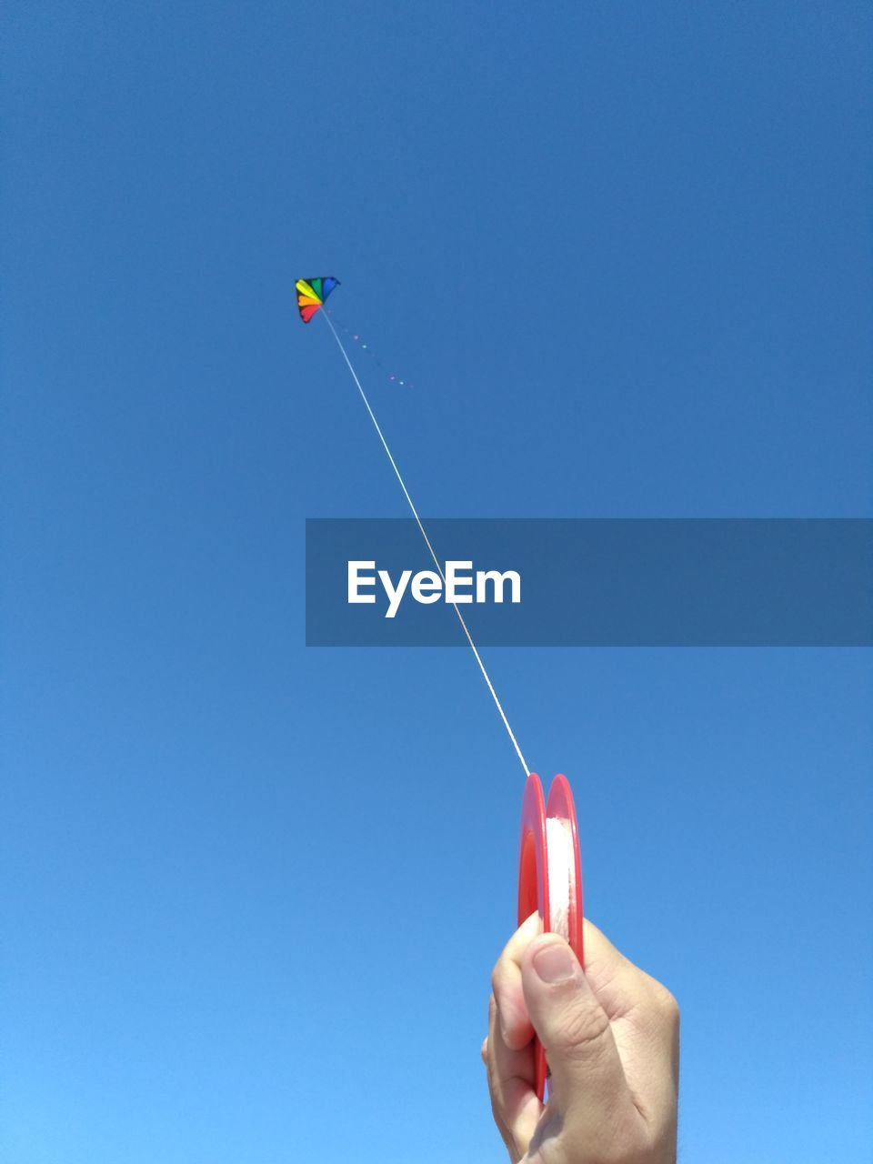 Close-up of person flying kite against clear sky