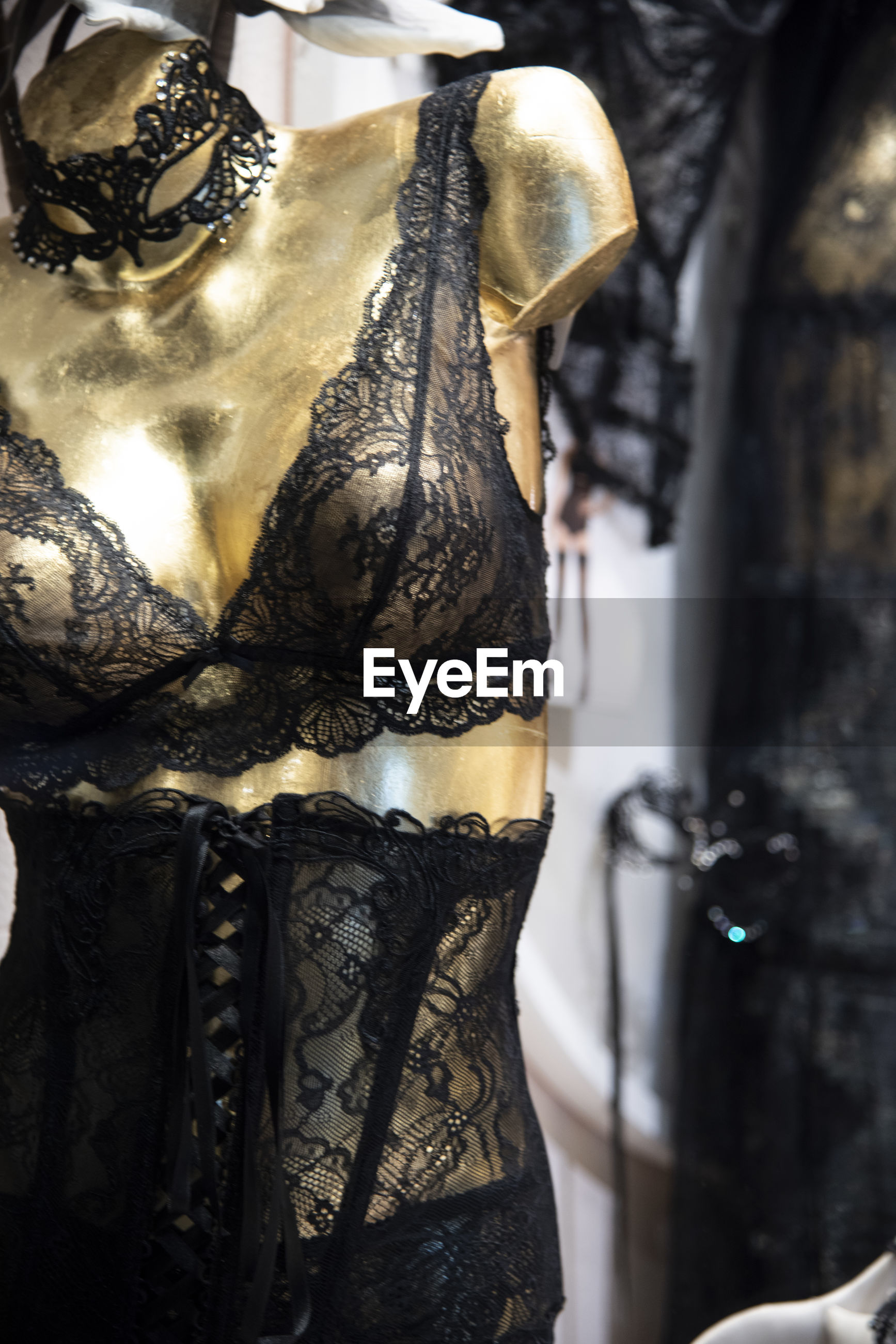 Black lace lingerie on gold mannequin. transparent woman bra and bustier.