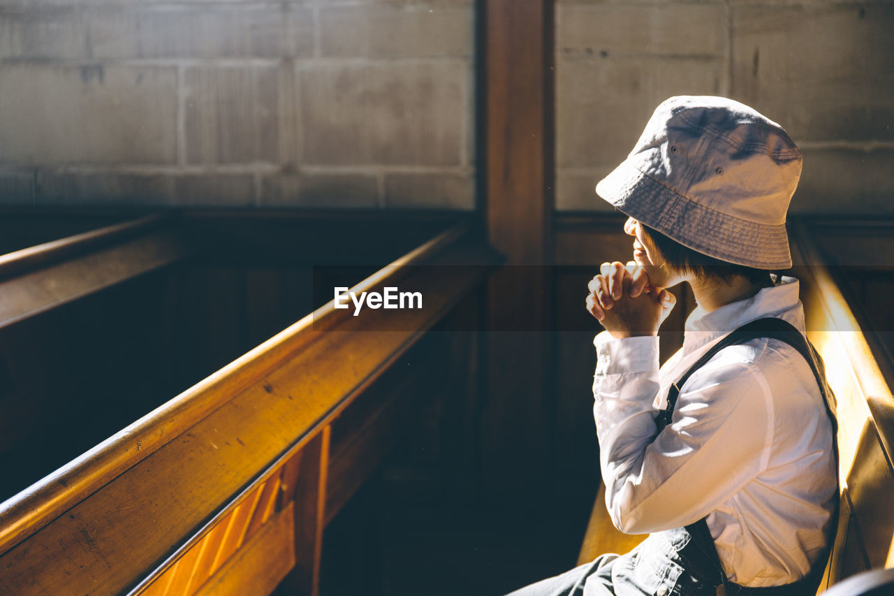 Side View Of Woman With Hands Clasped Praying In Church