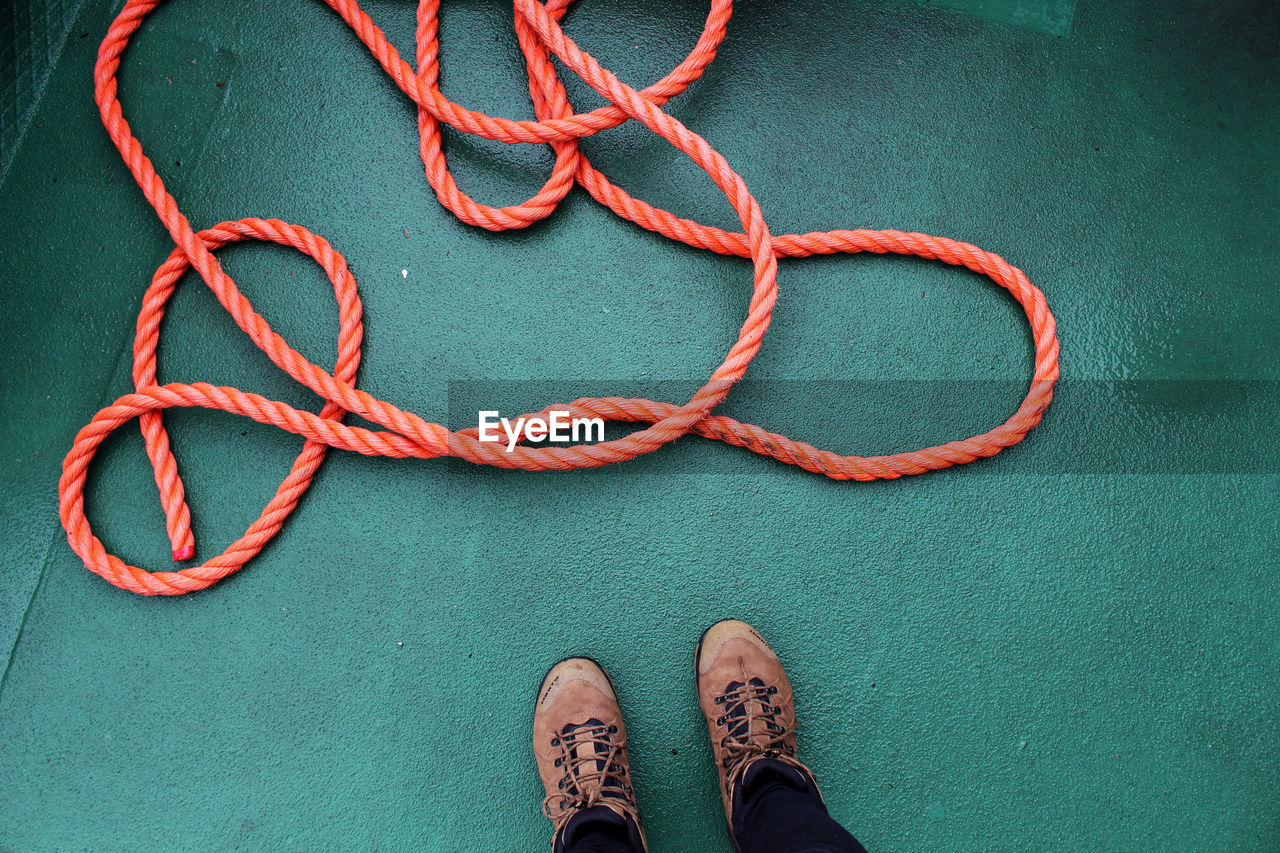 Low section of man standing by rope on boat deck