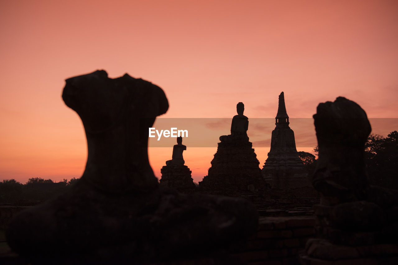 Low Angle View Of Silhouette Buddha Statues Against Sky During Sunset