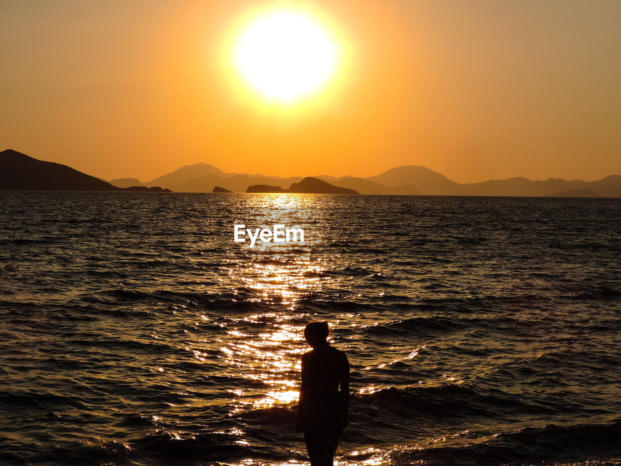 sunset, water, scenics - nature, sky, beauty in nature, sea, real people, silhouette, sun, standing, leisure activity, lifestyles, one person, sunlight, orange color, nature, idyllic, tranquil scene, tranquility, outdoors, lens flare, bright