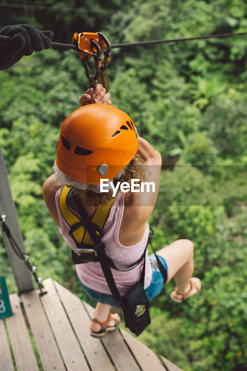 Full Length Of Woman Hanging On Zip Line Over Trees