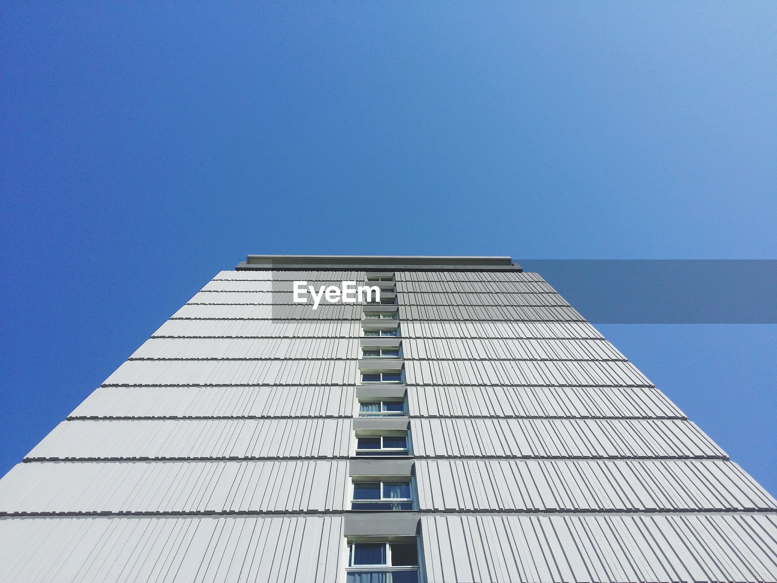 Low angle view of tall building against clear blue sky