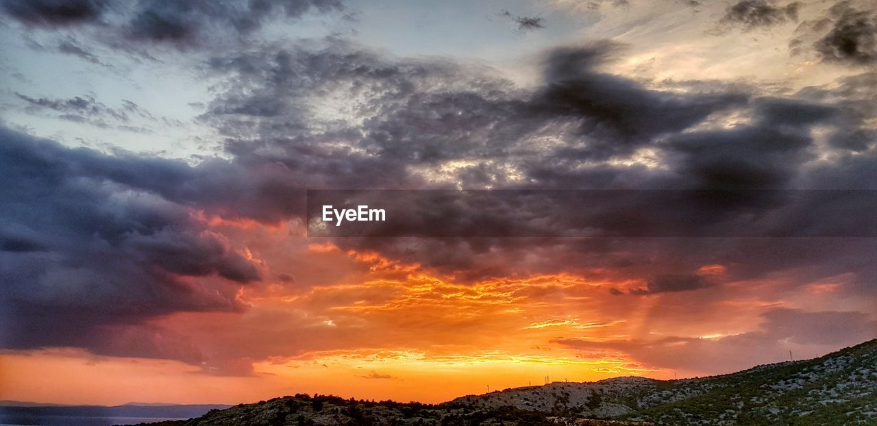 cloud - sky, sky, beauty in nature, sunset, scenics - nature, tranquil scene, tranquility, orange color, dramatic sky, nature, idyllic, no people, mountain, non-urban scene, outdoors, environment, low angle view, overcast, silhouette, ominous